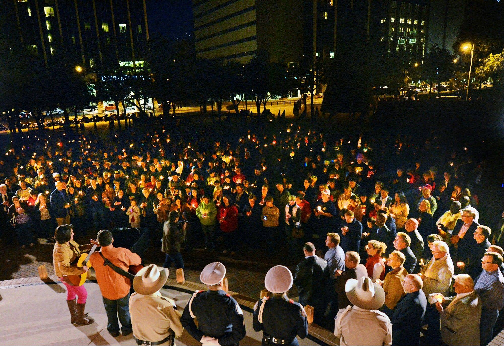 People gather Saturday in Centennial Plaza in Midland, Texas for a candlelight vigil held in honor of four veterans who were killed when a freight train hit a parade float Thursday.