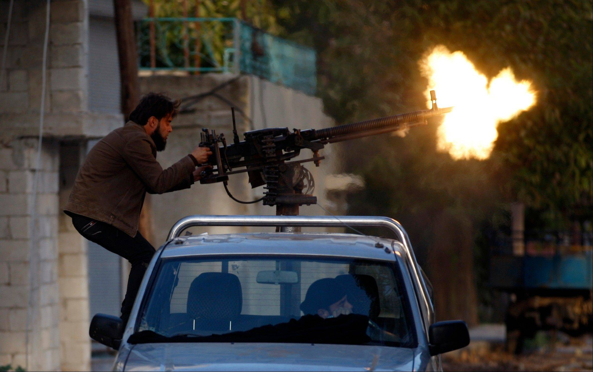 A Syrian fighter shoots during clashes with Syrian army forces in the town of Harem on the outskirts of Idlib, Syria.