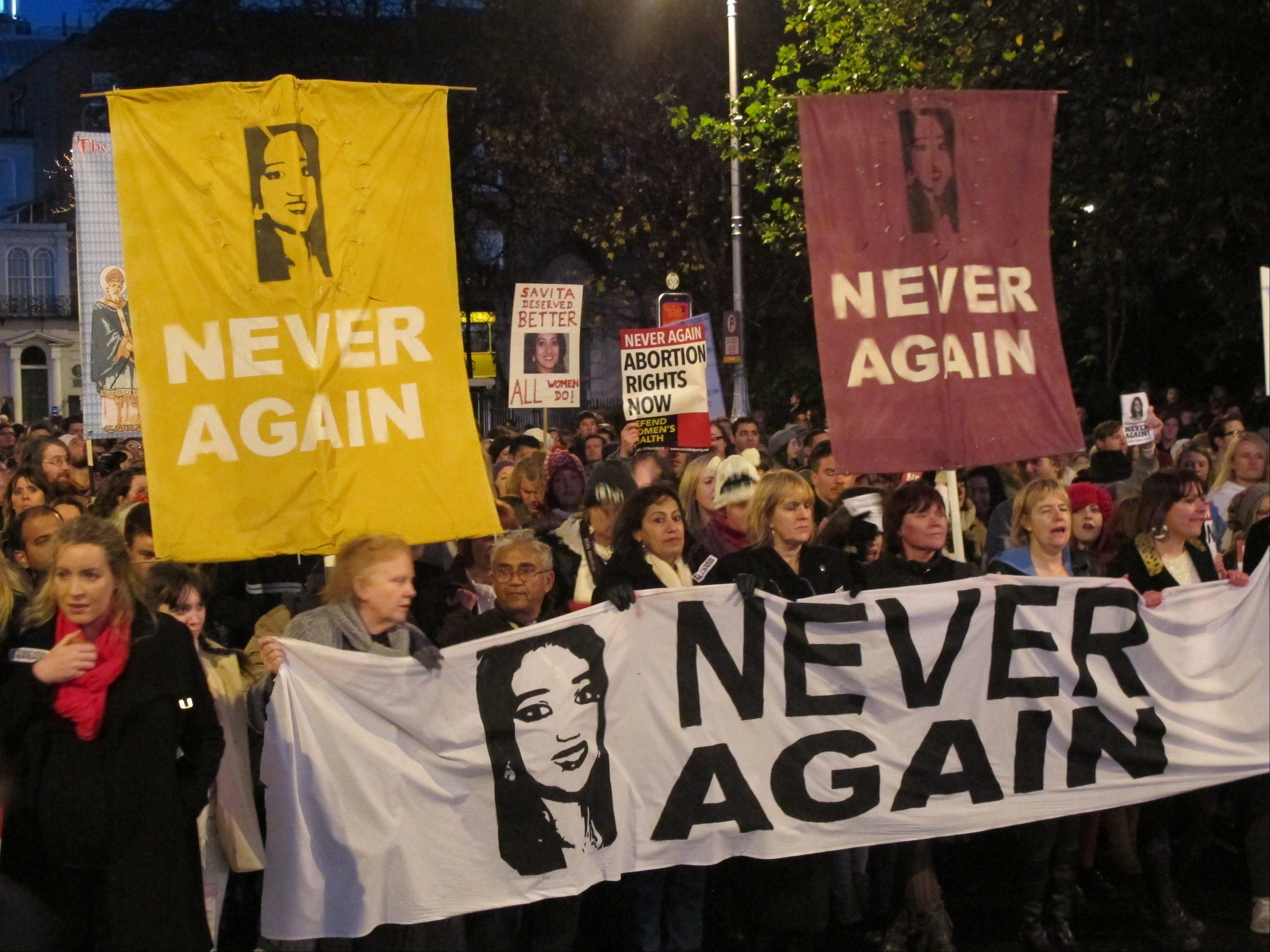 Abortion rights protesters bearing pictures of Savita Halappanavar march Saturday through central Dublin.