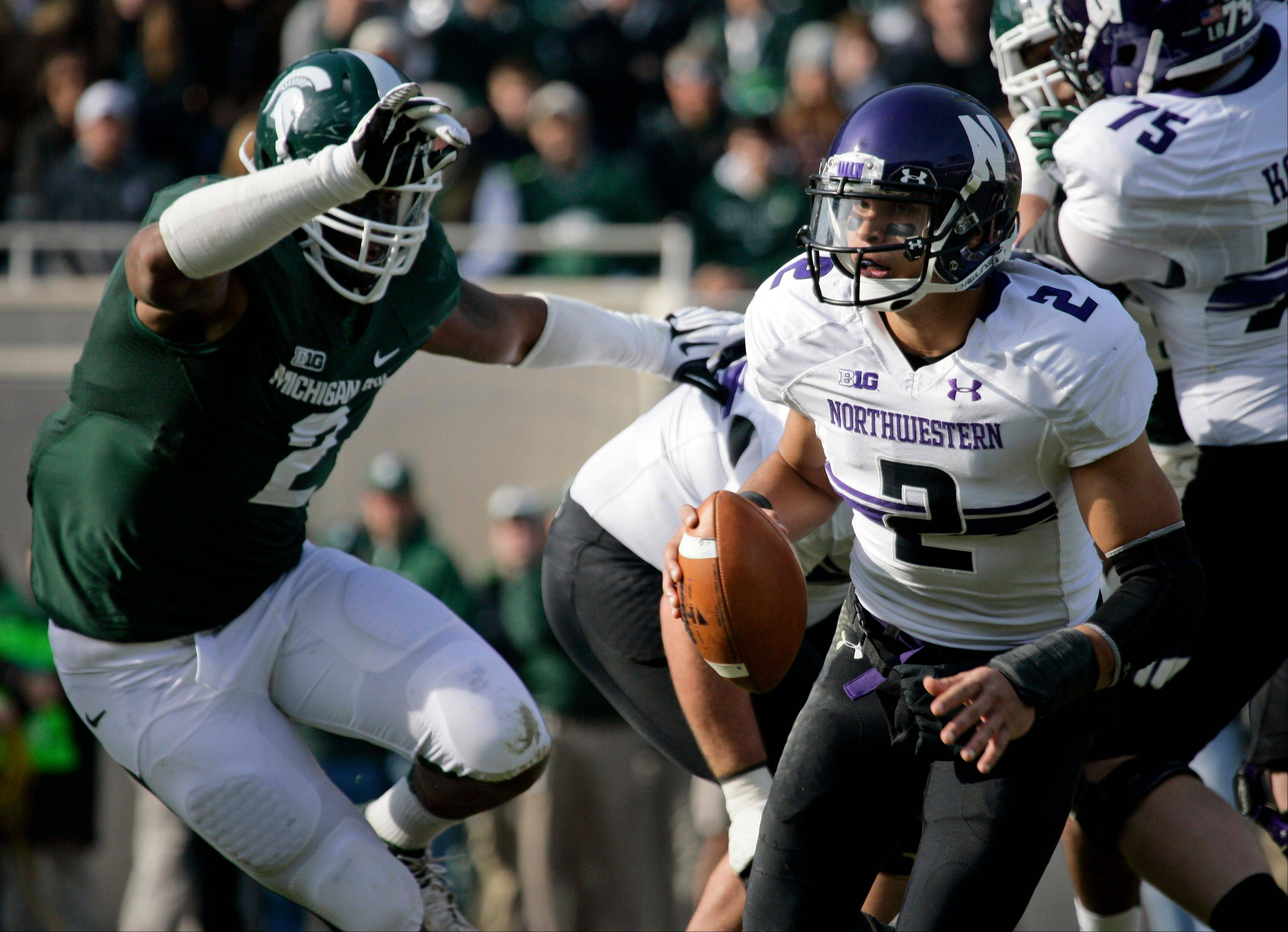 Northwestern quarterback Kain Colter, right, scrambles against Michigan State's William Gholston during the first quarter.