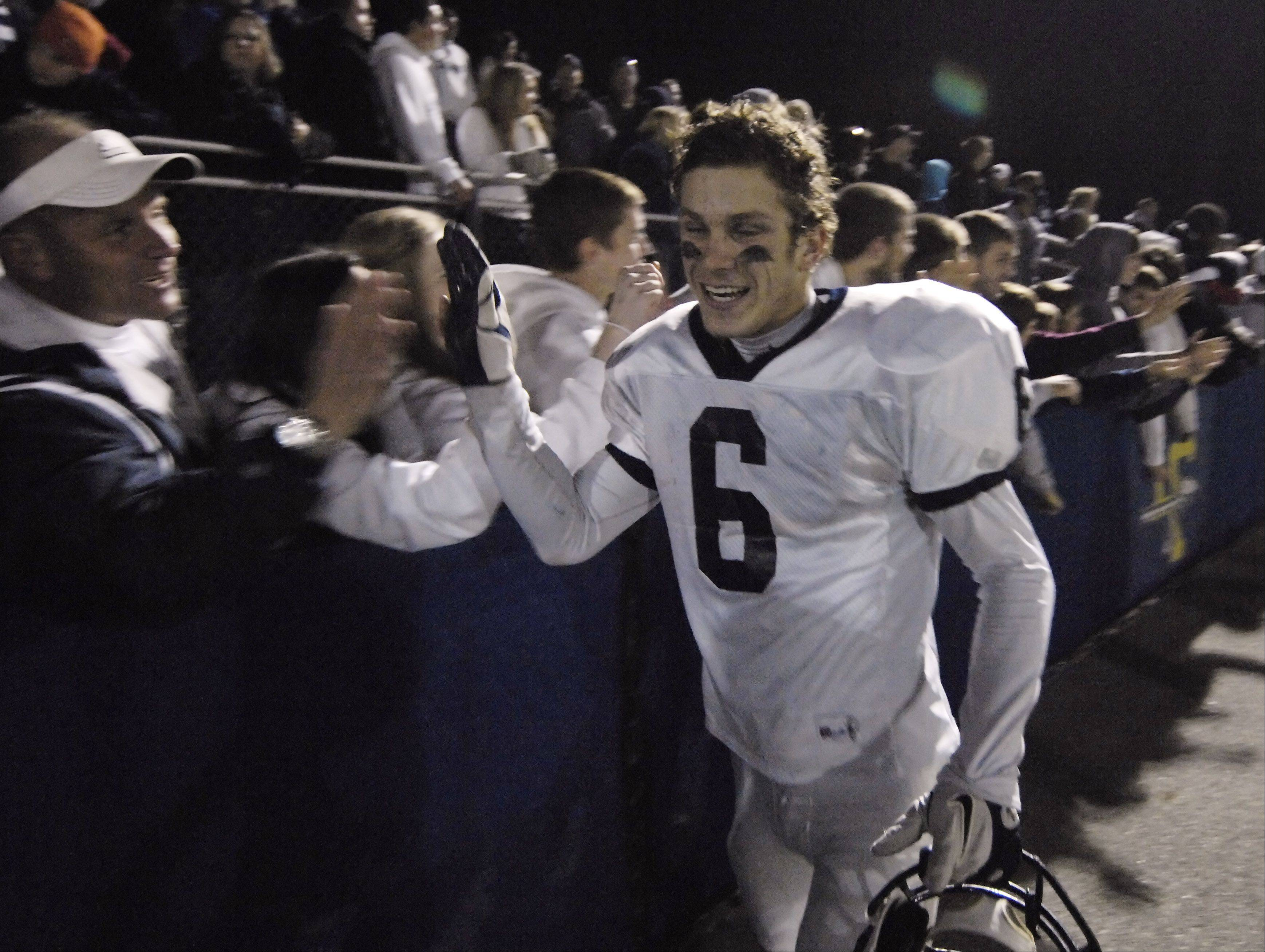 Cary-Grove's Marcus Thimios celebrates with fans after Saturday's victory over Lake Forest in the class 6A football semifinal.