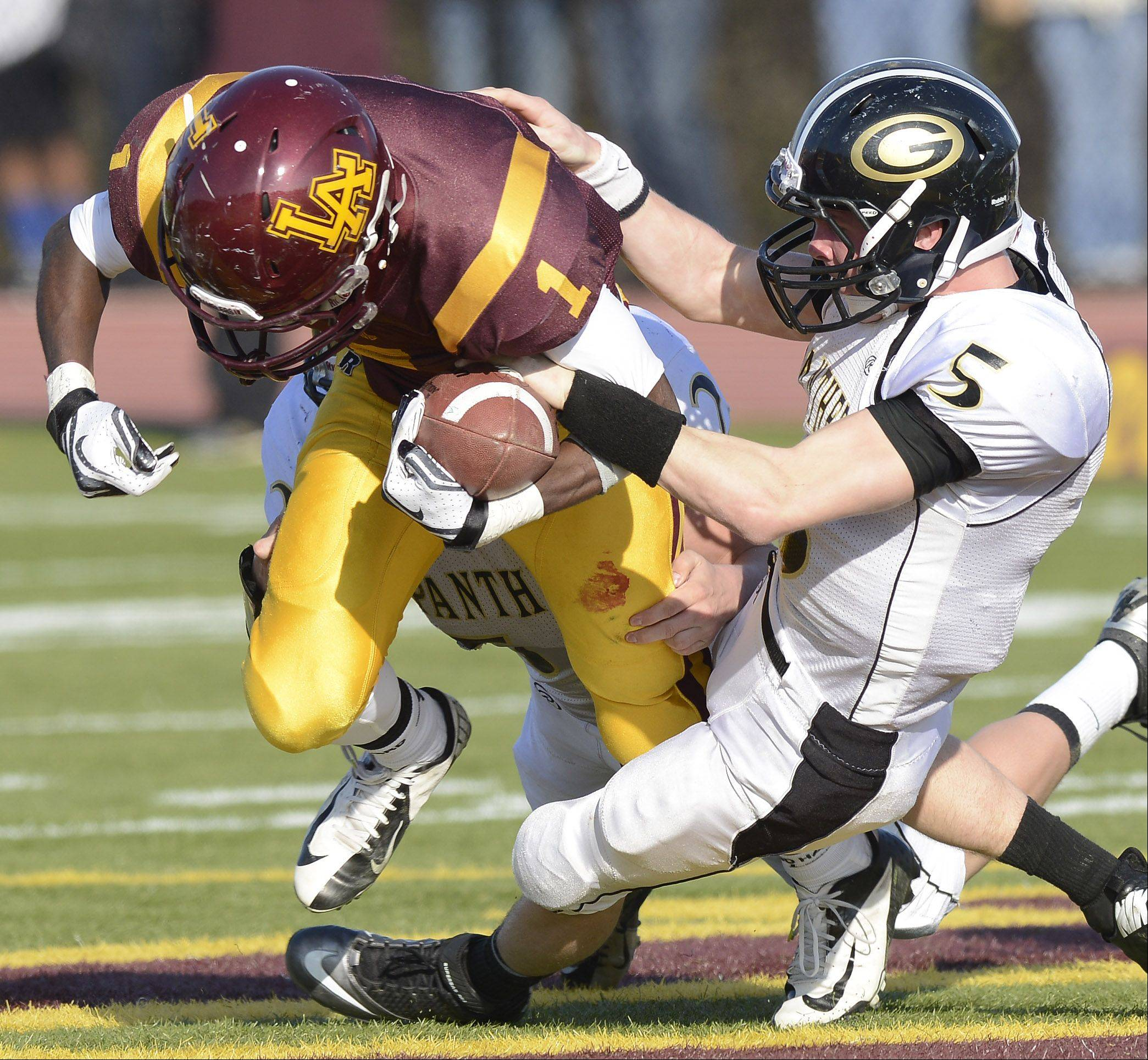 Glenbard North�s Brian Murphy, right, tries to strip the ball from Loyola Academy�s Kristopher Coker during Saturday�s class 8A football playoff semifinal.