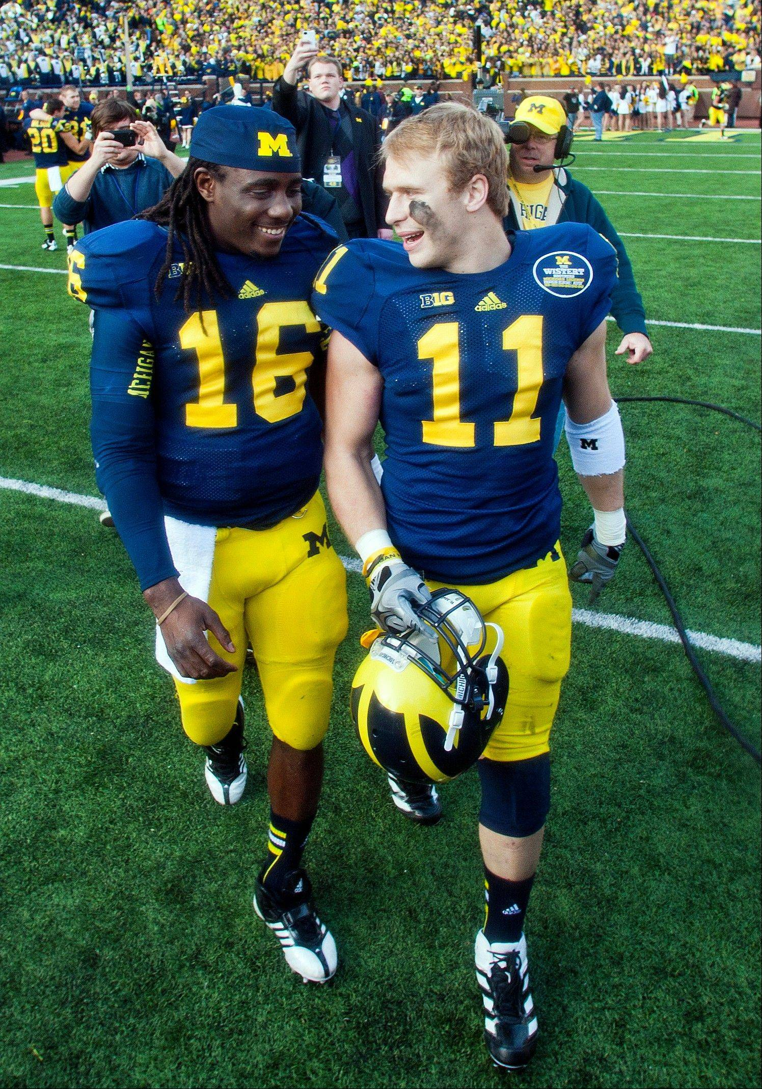 Michigan co-captains quarterback Denard Robinson (16) and safety Jordan Kovacs (11) walk off the field after playing their final home game in an NCAA college football game against Iowa, Saturday, Nov. 17, 2012, in Ann Arbor, Mich. Michigan won 42-17. (AP Photo/Tony Ding)