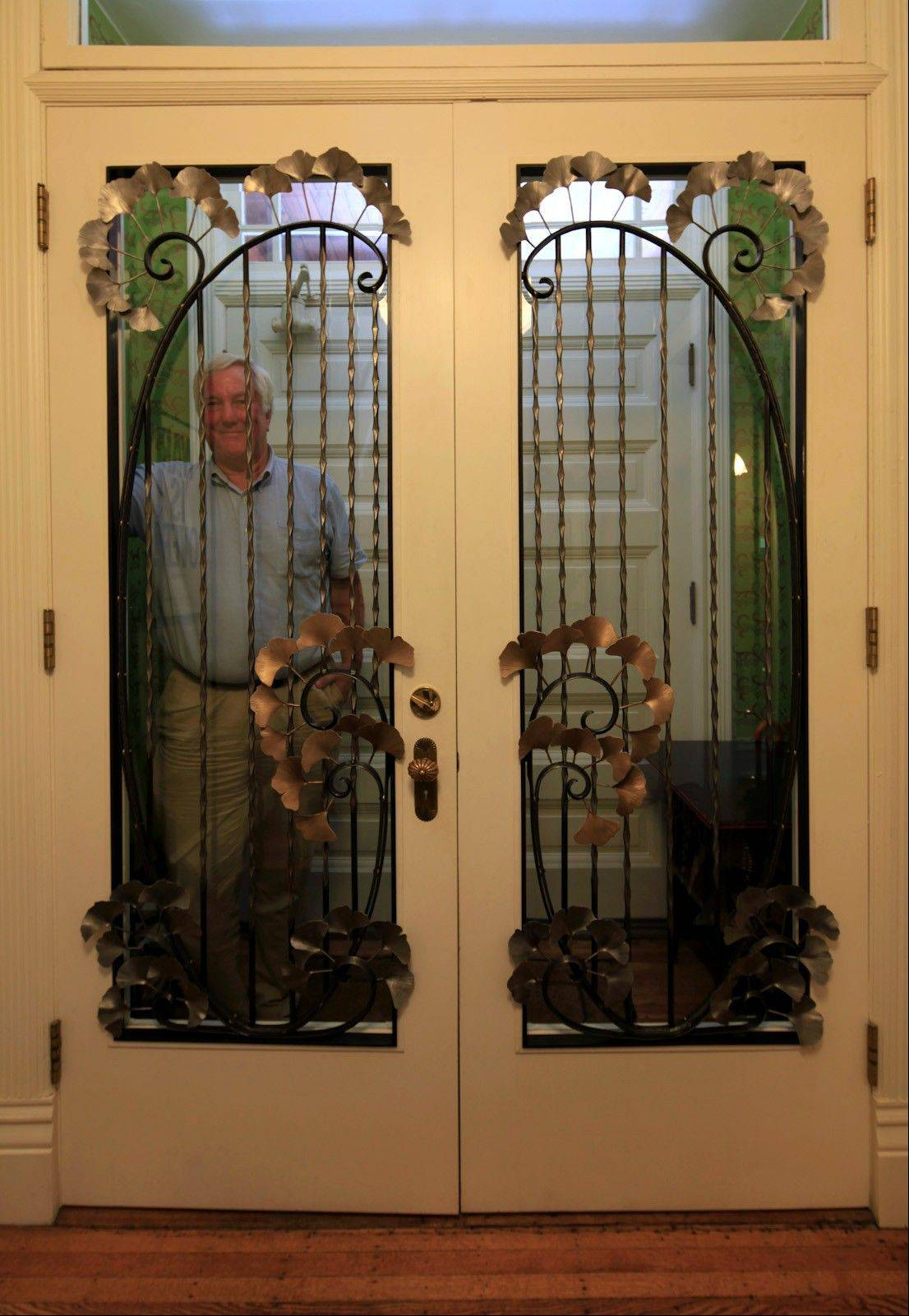 John Yust stands behind a ginkgo door he designed in collaboration with Chris Rand.
