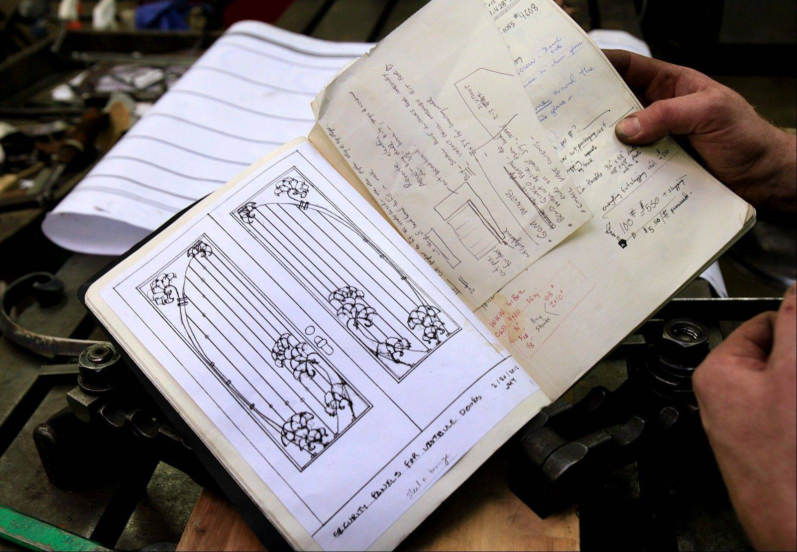 Metalsmith Chris Rand holds a notebook that shows the first design of the door he is working on.