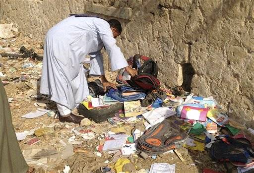 An Egyptian looks through books and school bags that were strewn along the tracks at the scene where a speeding train crashed into a bus carrying children to their kindergarten, killing at least 47, officials said, near Assiut in southern Egypt, Saturday, Nov. 17, 2012. The bus was carrying more than 50 children between 4 and 6 years old when it was hit by a train near al-Mandara village in Manfaloot district in the province of Assiut, a security official said, adding that it appears that the railroad crossing was not closed as the train sped toward it.