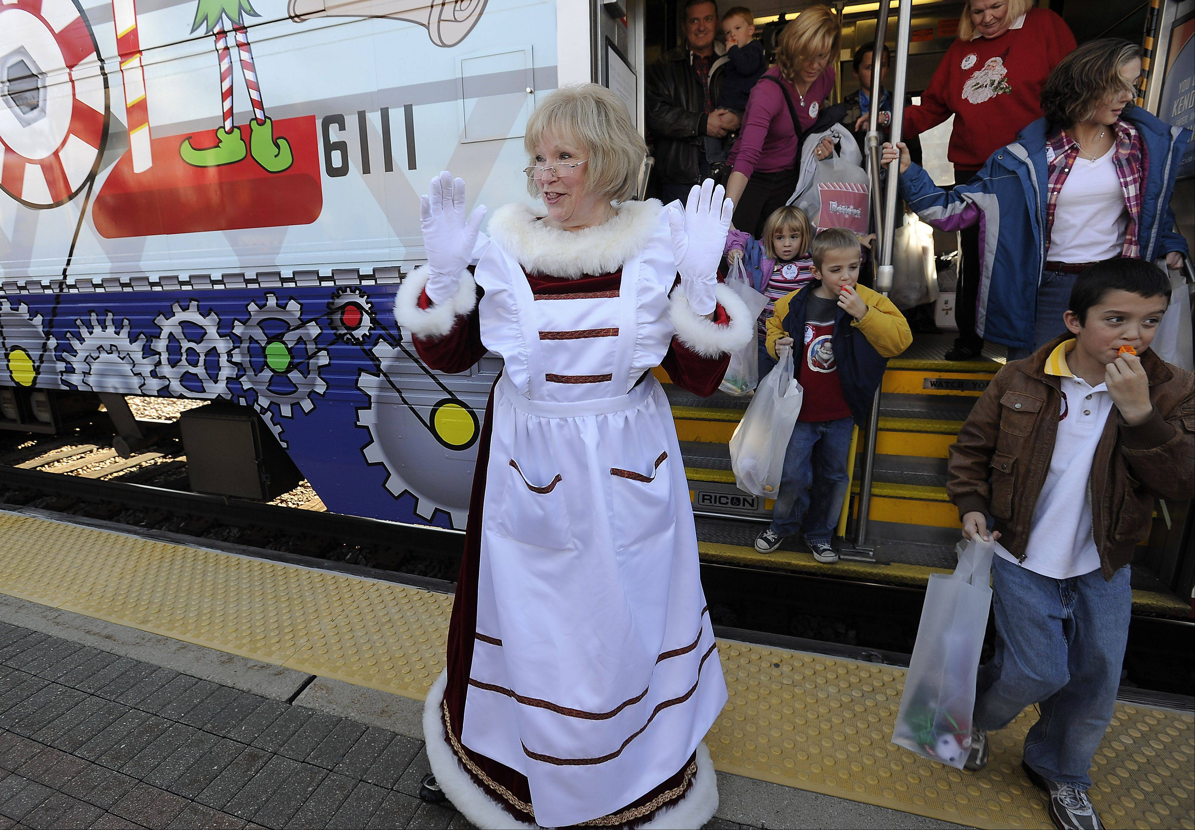 "Dressed as Mrs. Claus, Jan Stafford of Chicago steps off the ""Polar Express"" train ride for families of children with previous or terminal health problems on Saturday in Des Plaines. Operation North Pole hosted the annual event designed to bring a day of fun and fantasy to families dealing with health issues in at least one of their children."