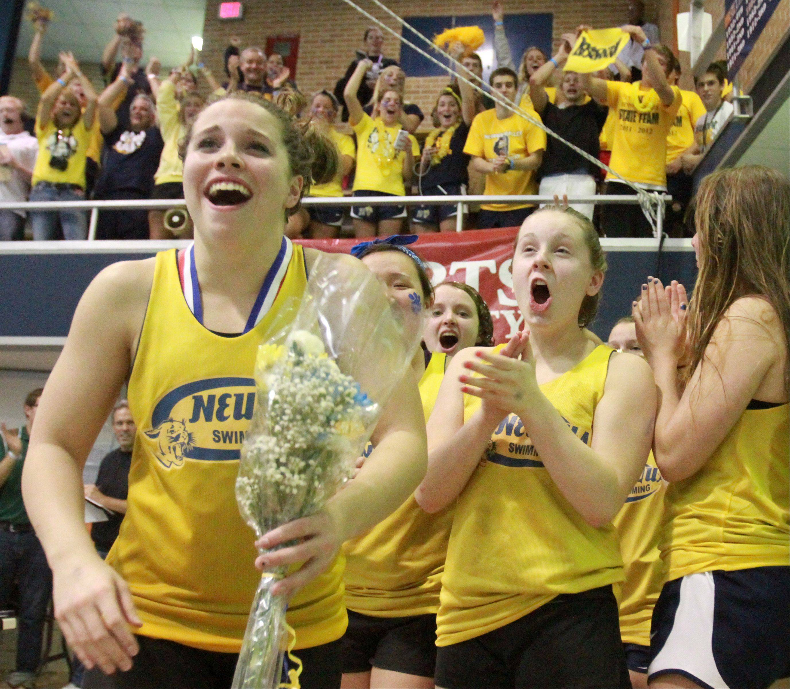 Neuqua Valley celebrates placing third, with their fans in the background, at the IHSA state championships in Evanston on Saturday.
