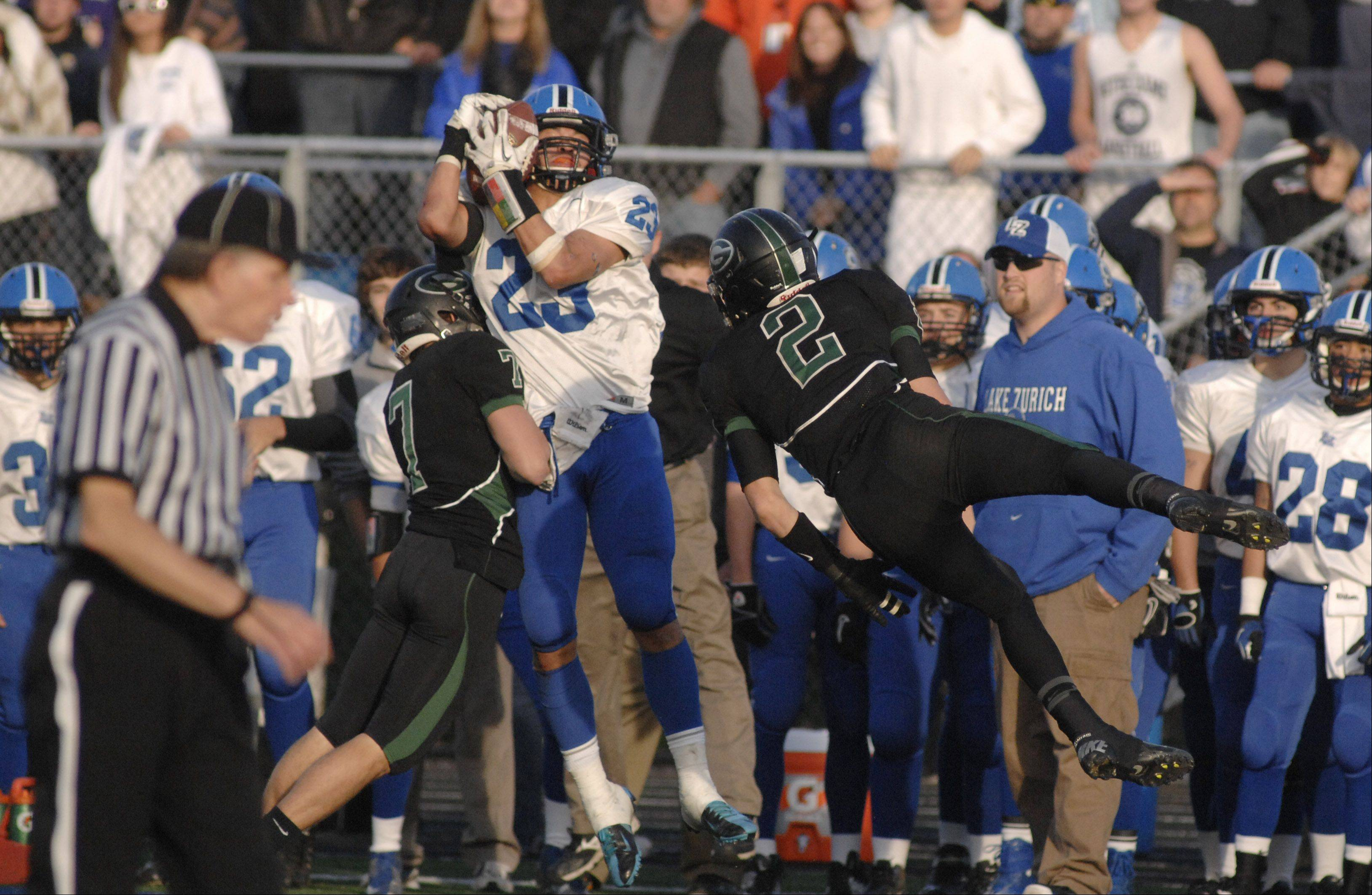 Lake Zurich's Grant Soucy completes a pass despite blocking attempts by Glenbard West's Charlie Sweeney and Joe Marconi in the fourth quarter on Saturday, Nov. 17.