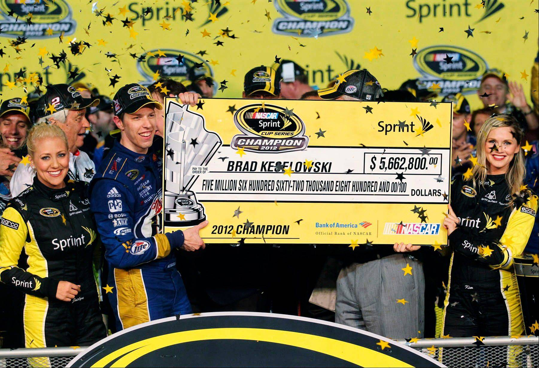 Brad Keselowski holds up an oversized check after winning the NASCAR Sprint Cup Series championship following an auto race at Homestead-Miami Speedway in Homestead, Fla. Keselowski clinched the title after fellow contender Jimmie Johnson pulled out of the season finale because of a parts failure. Jeff Gordon won the race.