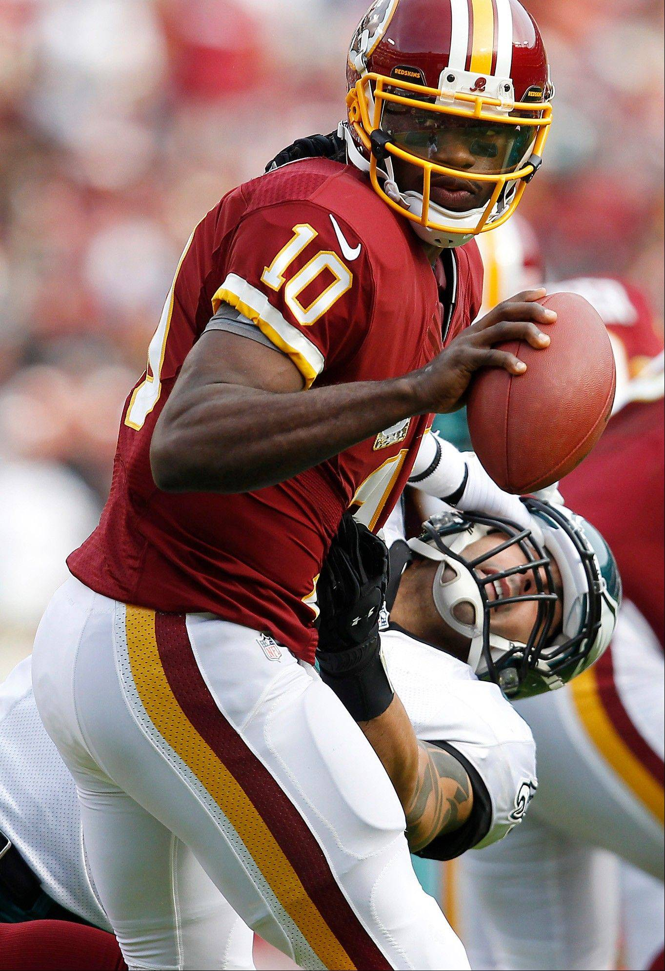 Eagles' Jason Babin, right, is stiff-armed by the Redskins' Robert Griffin III during the 2nd quarter as the Philadelphia Eagles play the Washington Redskins at FedEx Field in Landover, MD, Sunday.