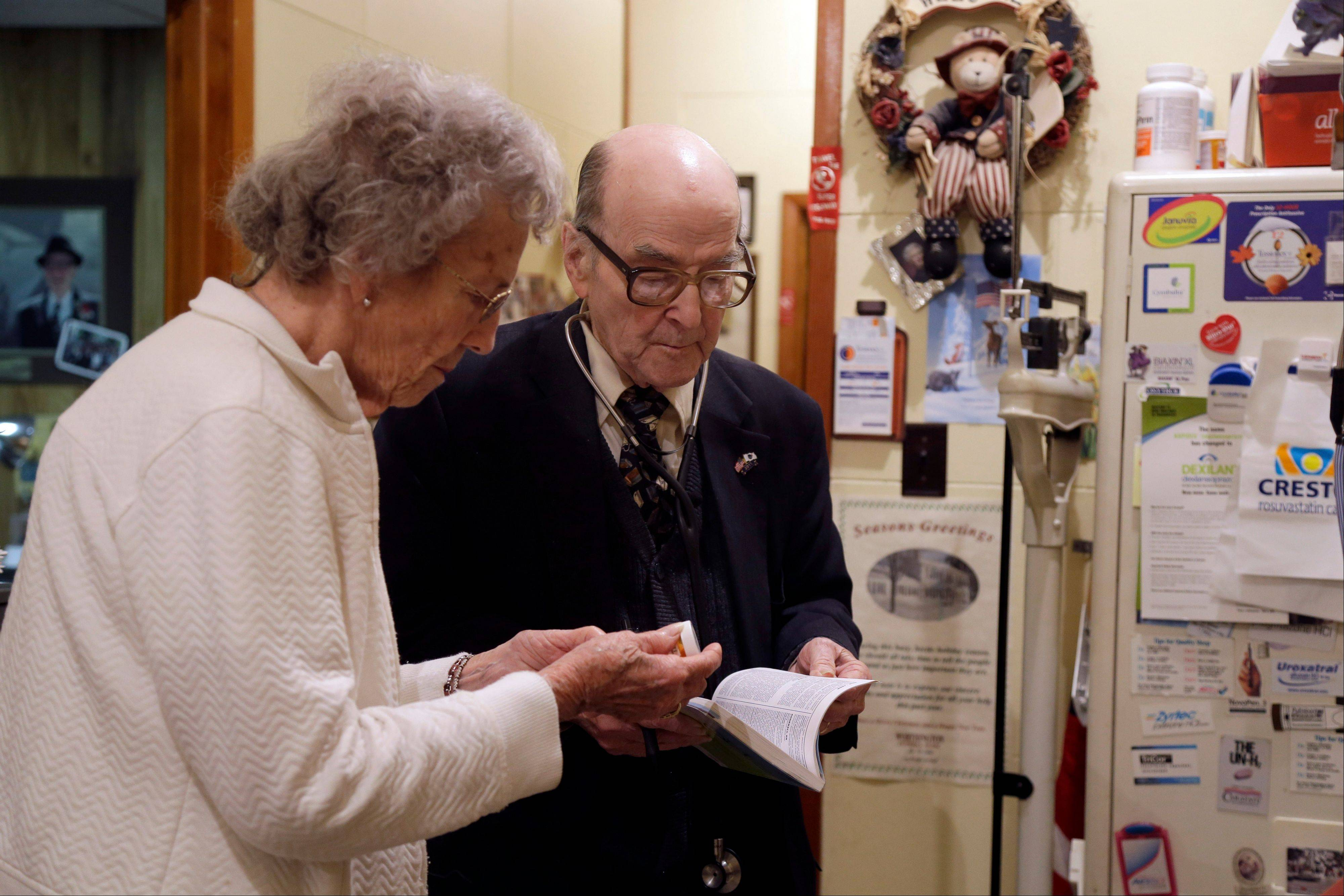 Dr. Russell Dohner talks with nurse Rose Busby about a patient's prescription in Rushville, Ill. In an era of rising health care costs, the 87-year-old doctor only charges patients $5 per office visit and doesn't take insurance saying it isn't worth the bother.