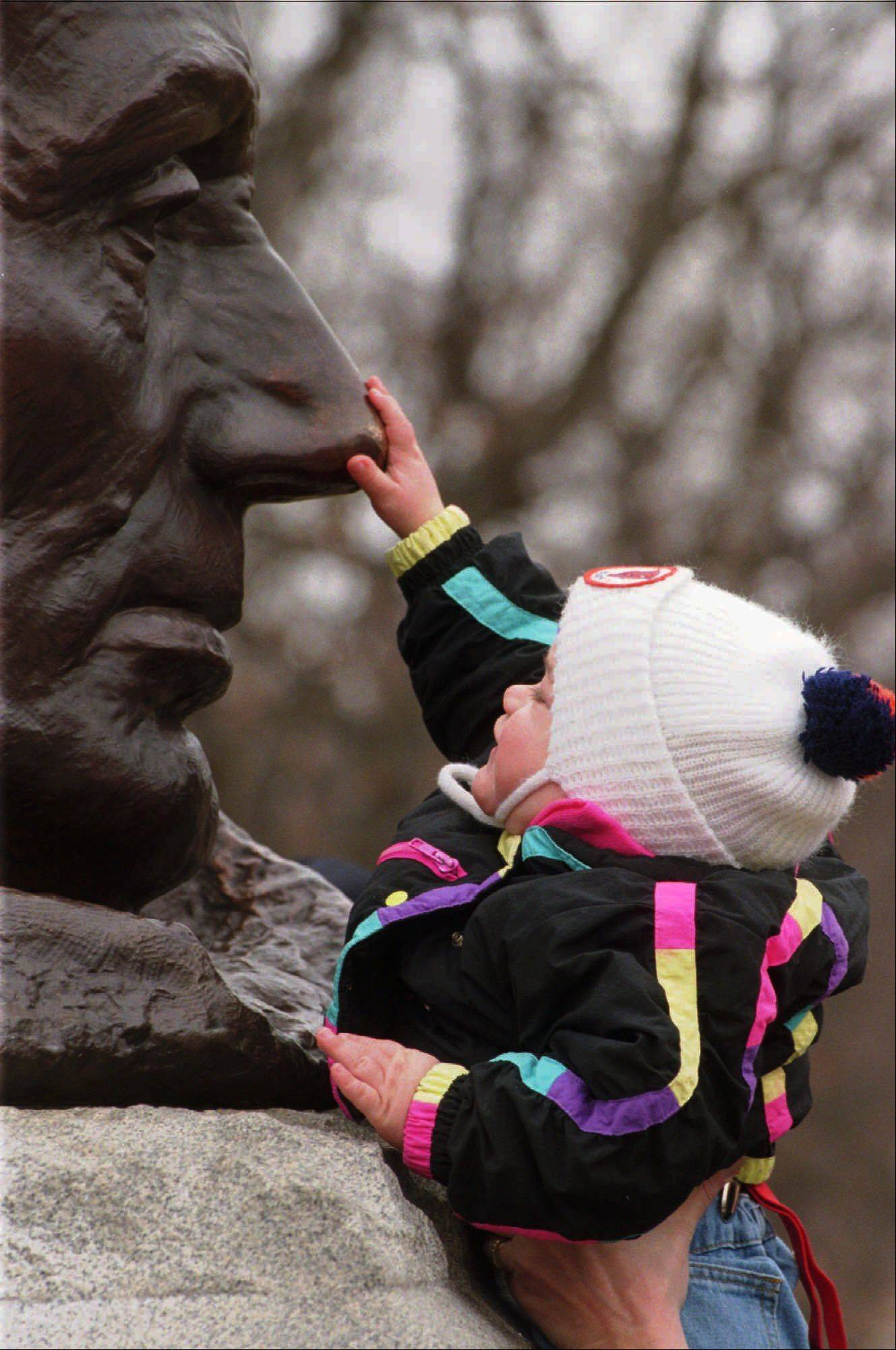 A youngster stretches to rub the nose of Abraham Lincoln, for good luck as tradition has it, while attending Lincoln's Tomb in Springfield.