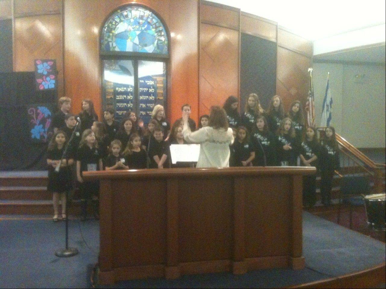 Gail Simon conducts the combined youth choir at the Interfaith Thanksgiving Celebration at Buffalo Grove's Congregation Beth Am Sunday.