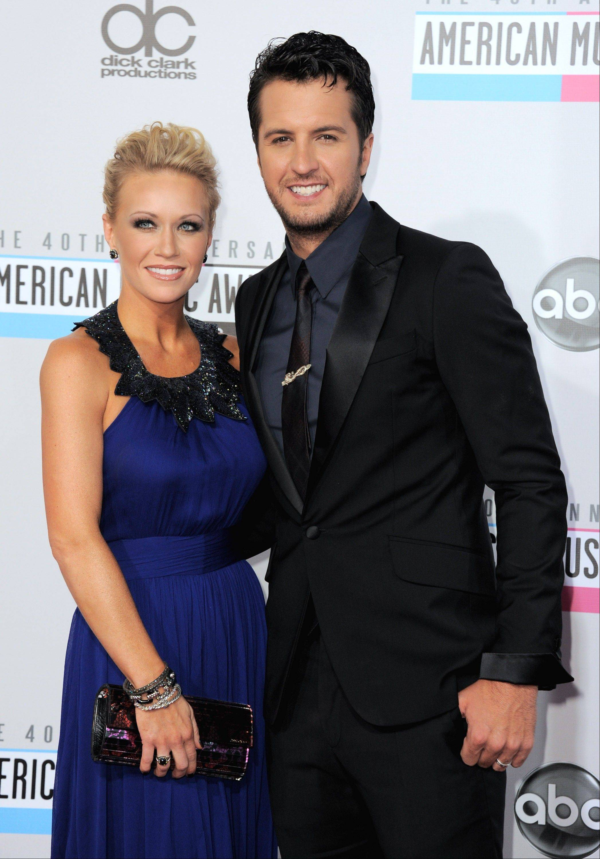 Country singer Luke Bryan, right, and Caroline Boyer arrive at the 40th Anniversary American Music Awards.