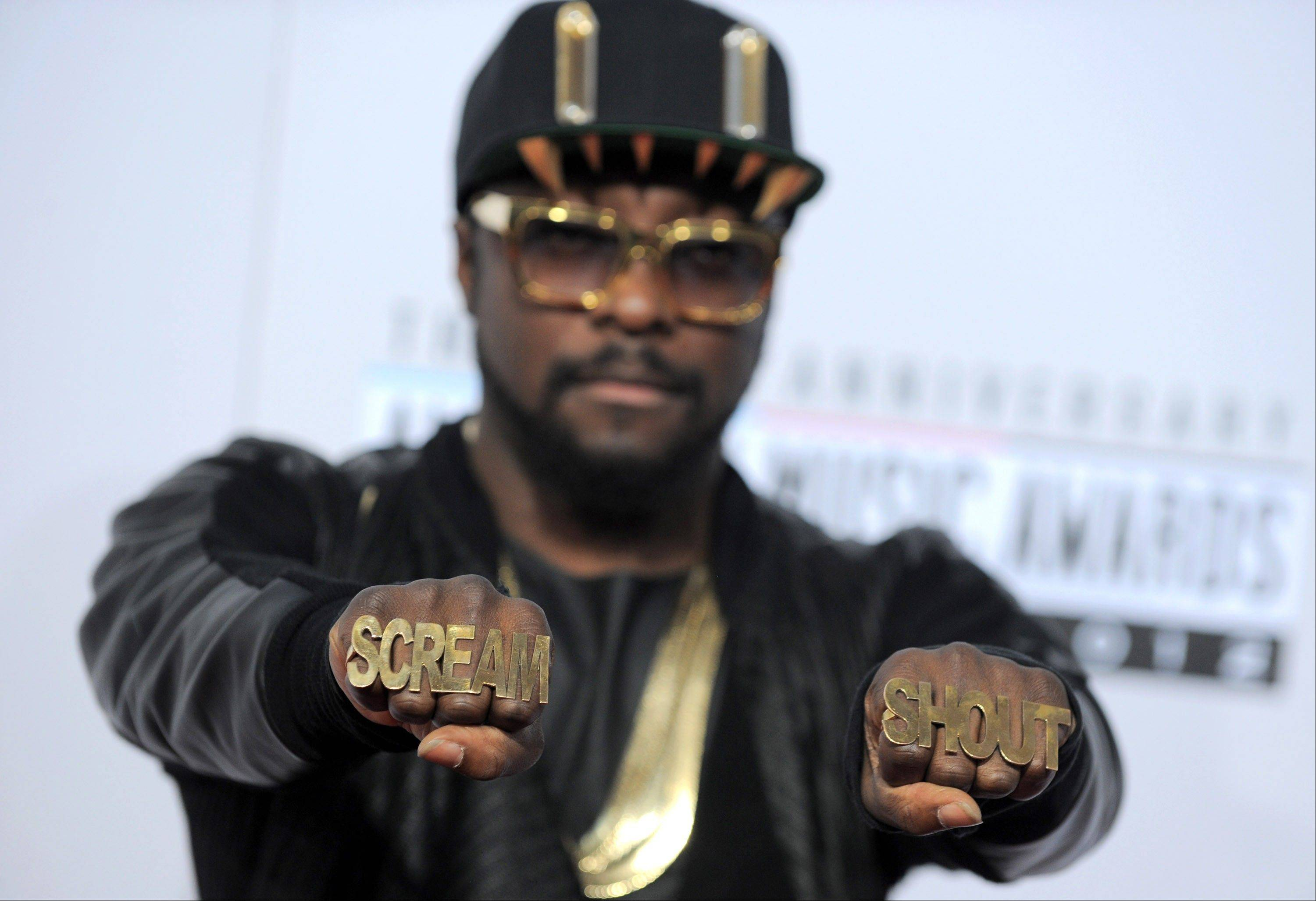 Will.i.am shows off his hardware while walking the press line ahead of the AMAs.