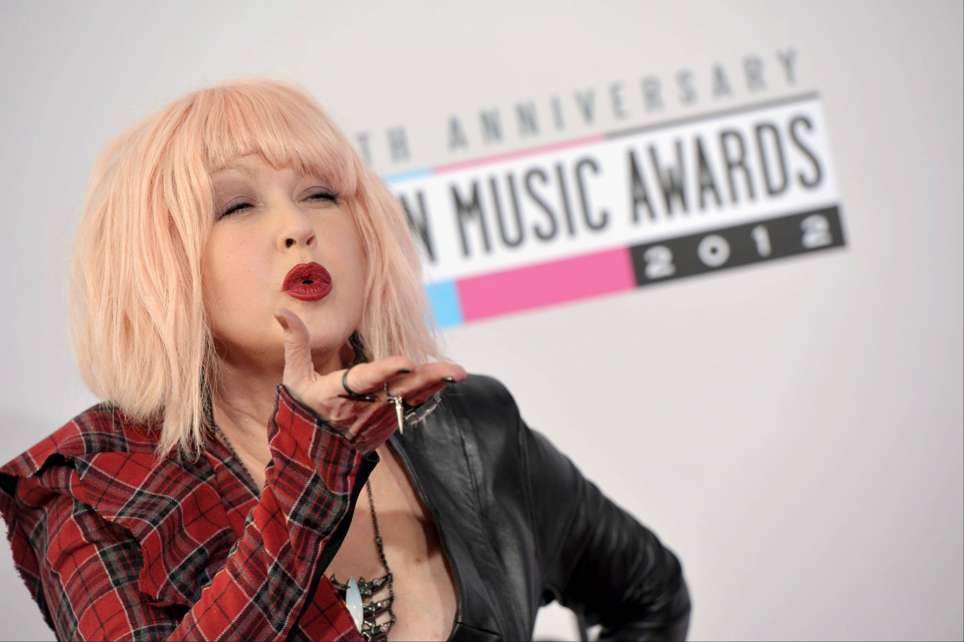 Cyndi Lauper shows fans some love while walking the press line before the 40th Anniversary American Music Awards on Sunday, Nov. 18, 2012, in Los Angeles.