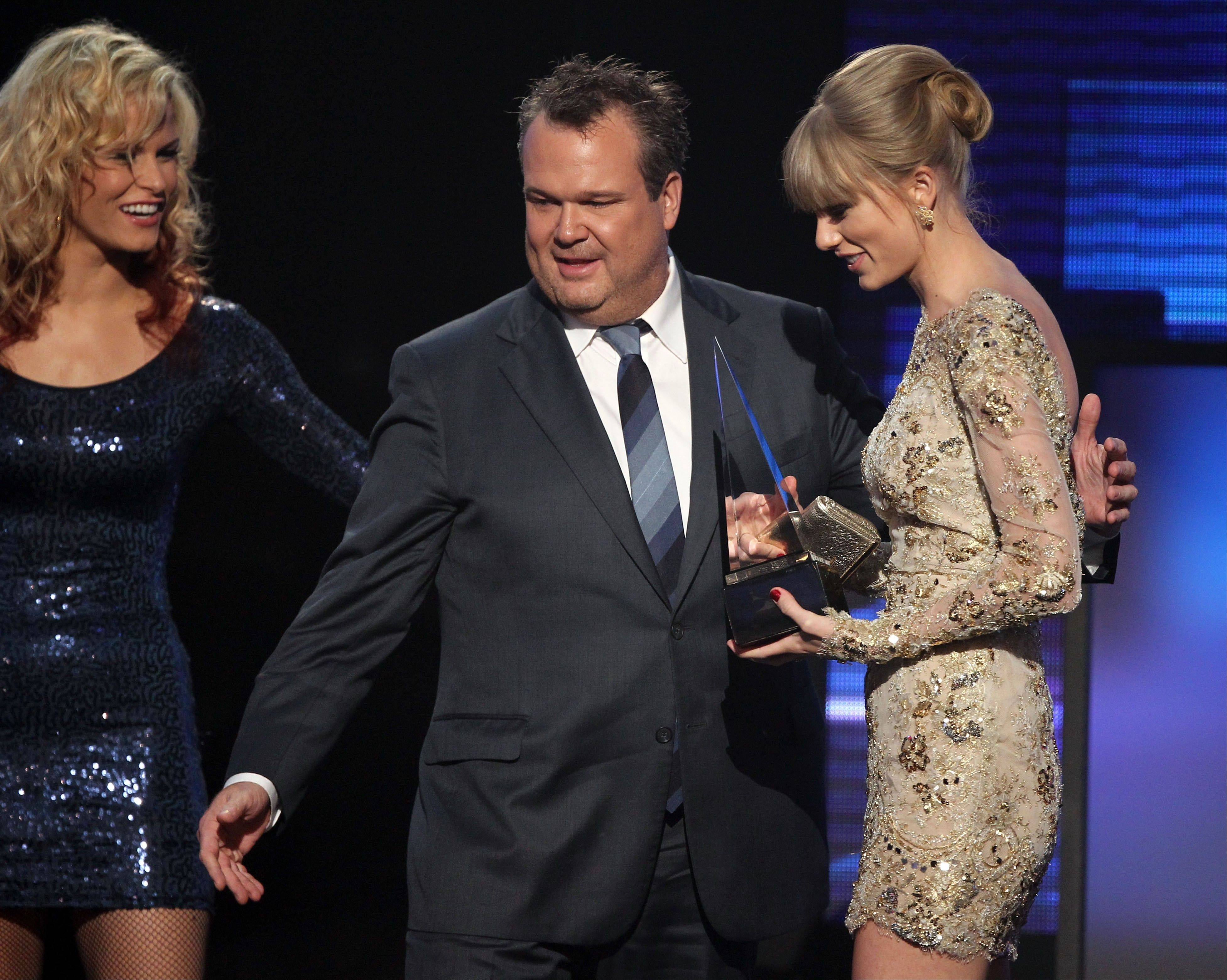 Taylor Swift accepts the award for favorite female country artist from presenter Eric Stonestreet at the 40th Annual American Music Awards on Sunday, Nov. 18, 2012, in Los Angeles.