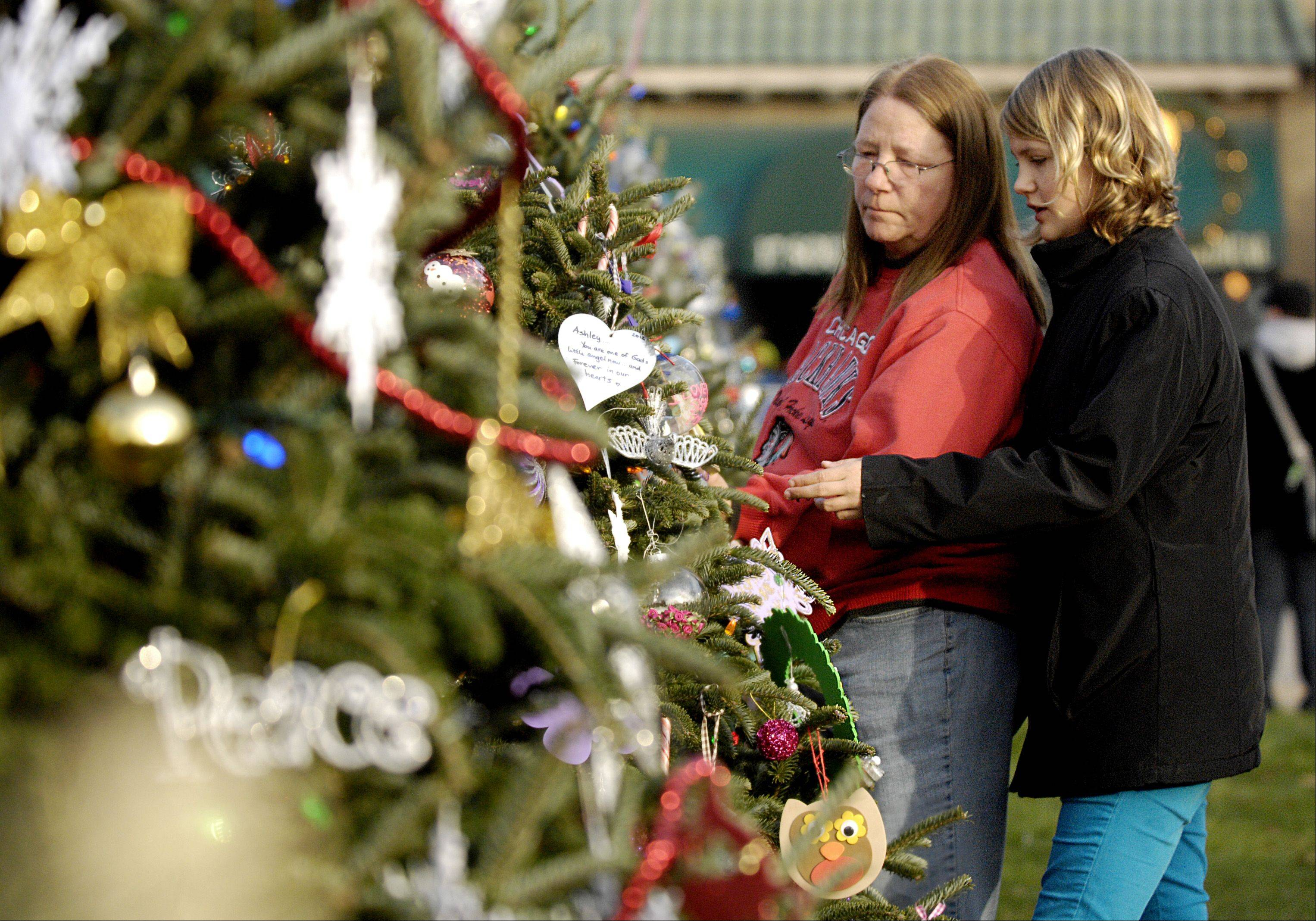 Paula and Emily Fox, 12, of Elmhurst, look over a Christmas tree in memory of Ashley Garza during the Bensenville Holiday Magic events Sunday in the Town Center. Paula grew up in Bensenville and still comes to the holiday event every year.