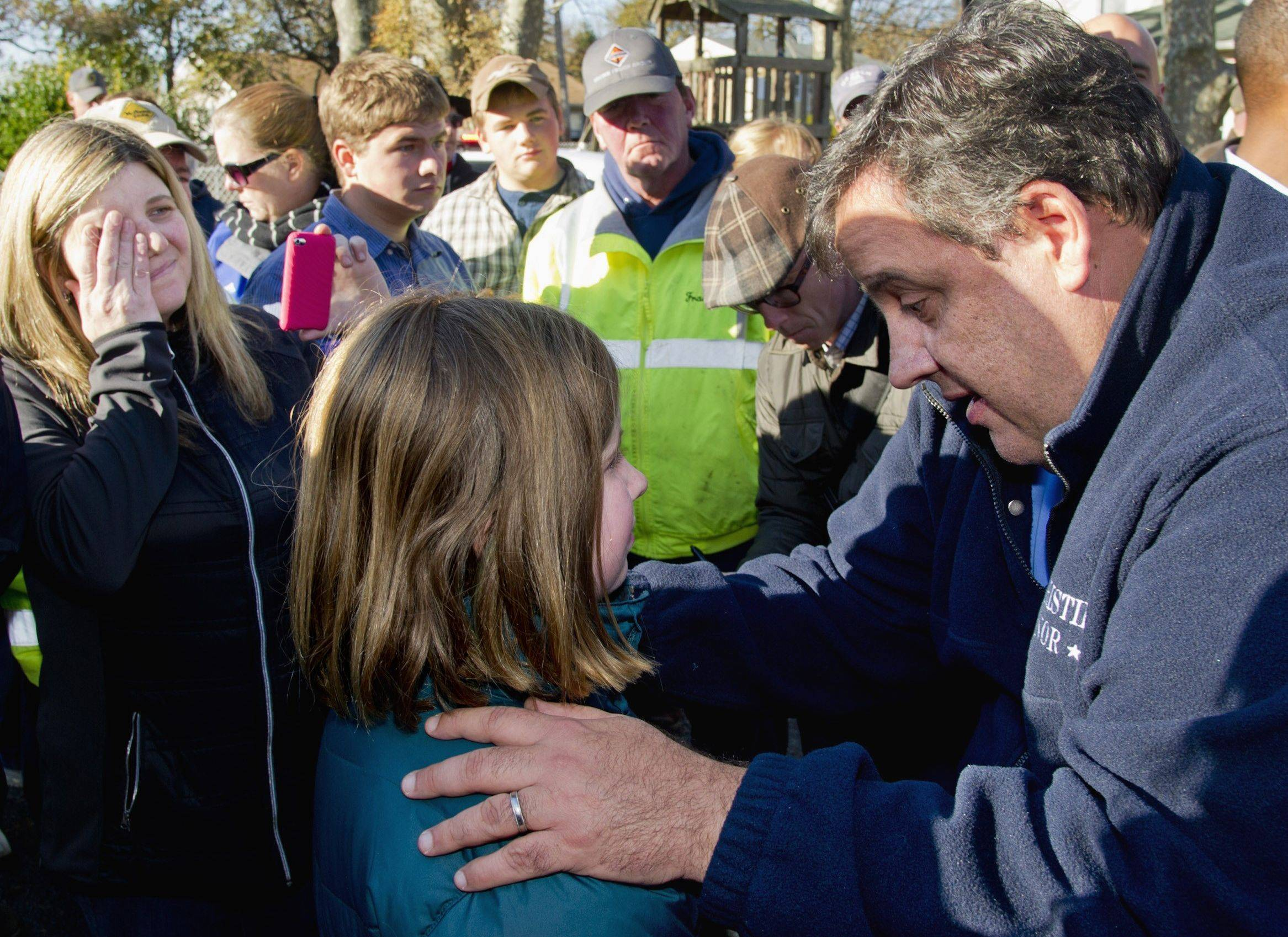 New Jersey Gov. Chris Christie gives 9-year-old Ginjer Doherty a pep talk outside in Port Monmouth, N.J., where he visited residents