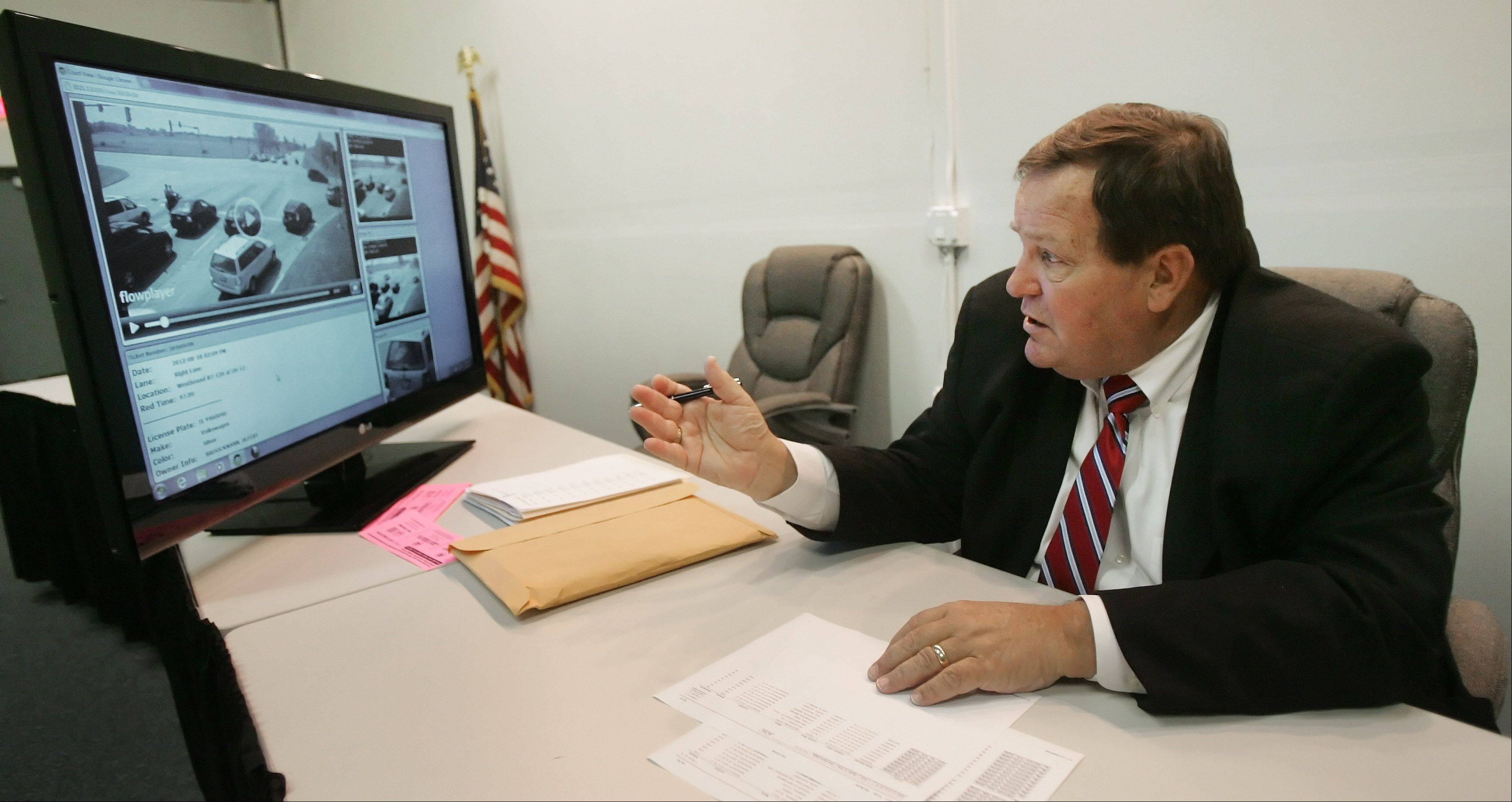 Former Lake County circuit court Chief Judge Henry Tonigan III reviews tape of one persons traffic stop as he presides over contested red-light camera violations at the Lakemoor Police Station. He also decides adjudication hearings for small ordinance violations, such as dog-at-large violations.