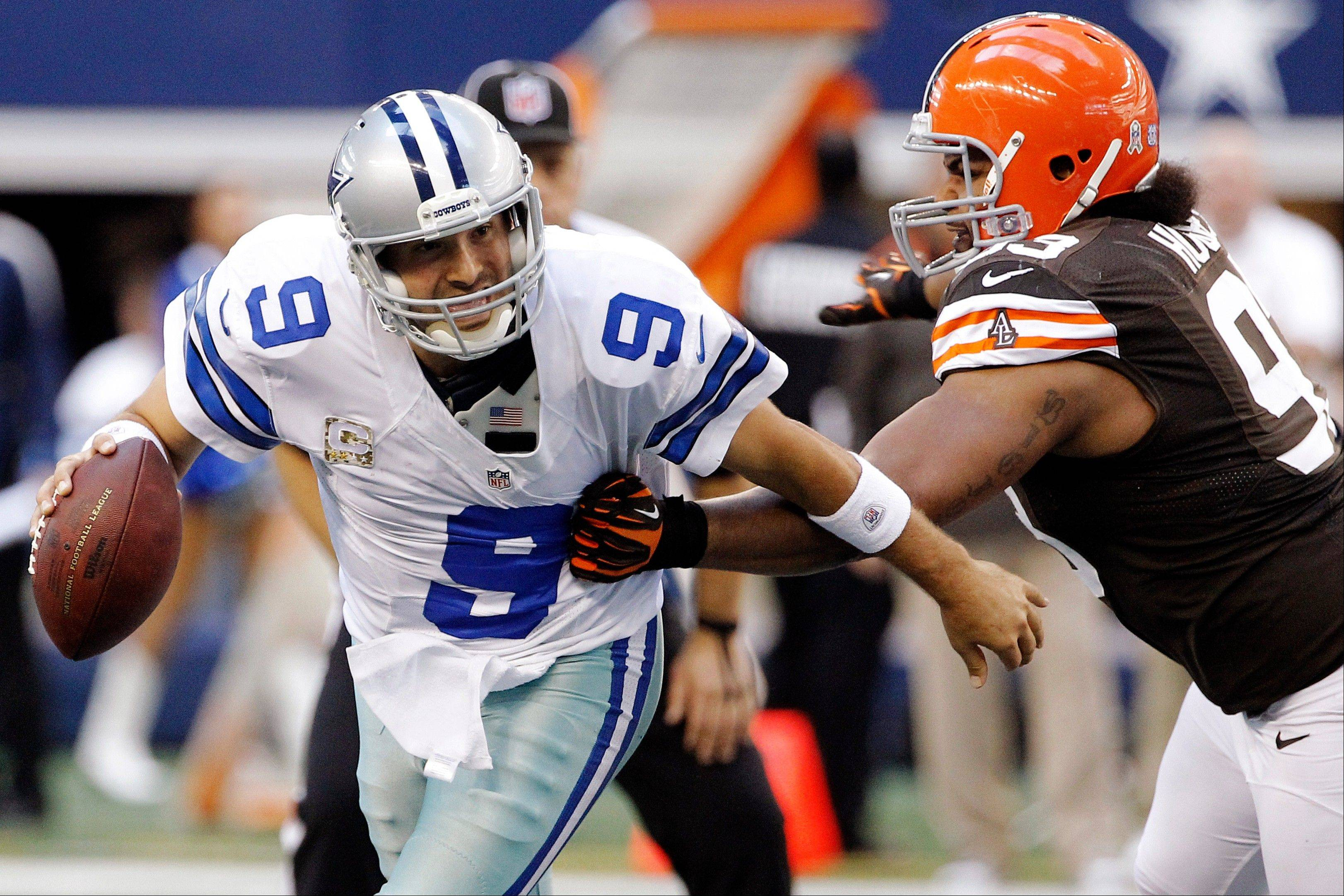 Dallas Cowboys quarterback Tony Romo (9) escapes a tackle attempt by Cleveland Browns' John Hughes (93) in the second half Sunday in Arlington, Texas.