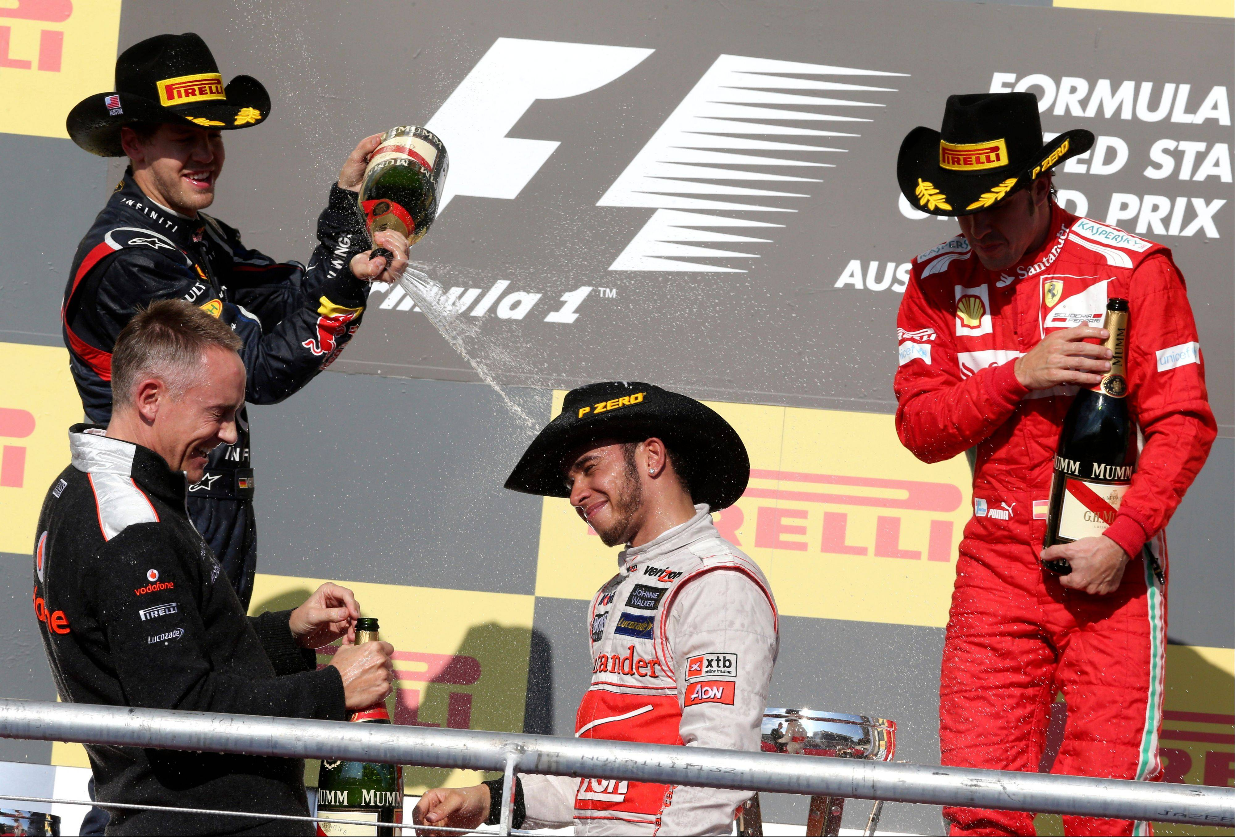 McLaren Mercedes driver Lewis Hamilton, center, of Britain, is sprayed by Red Bull driver Sebastian Vettel, top left, of Germany after Hamilton won the Formula One U.S. Grand Prix auto race at the Circuit of the Americas Sunday in Austin, Texas. Ferrari driver Fernando Alonso, right, of Spain finished third.