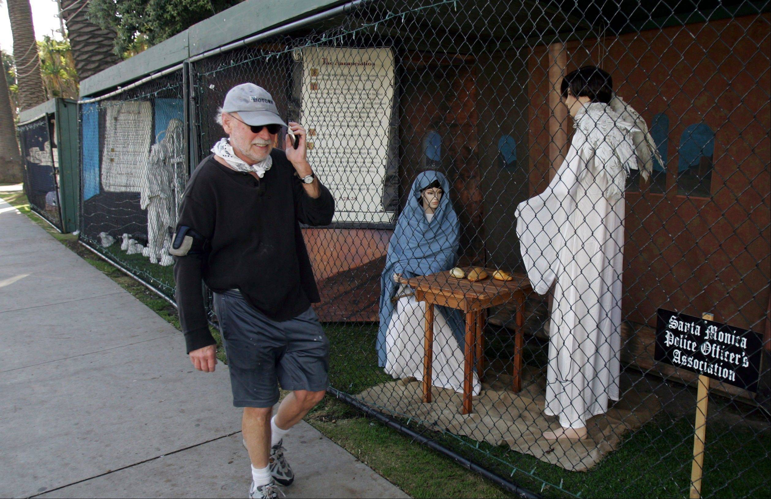 A man walks past two of the traditional Nativity scenes in Santa Monica, Calif., last December.