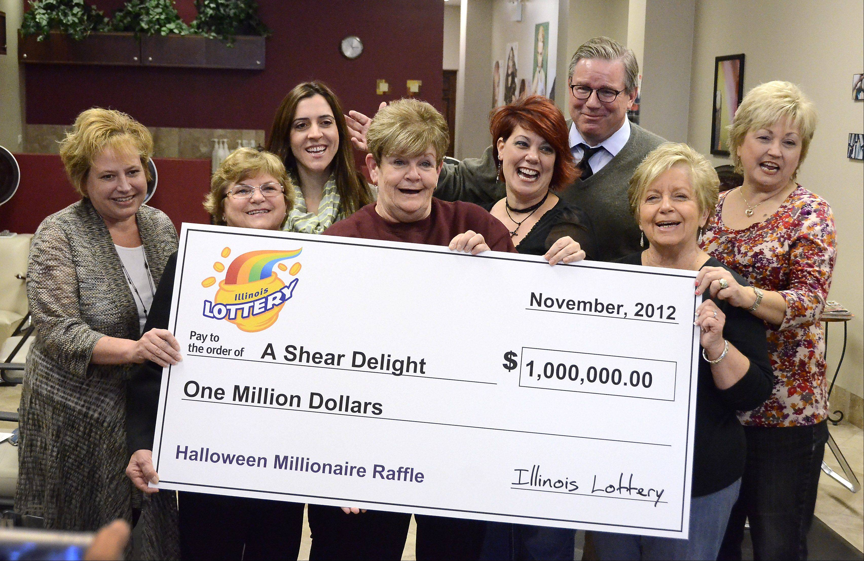 Illinois Lottery Superintendent Michael Jones presents a $1 million check to hair stylists at A Shear Delight in Hanover Park. Among the nine winners who pool their money every week are, from left, Barb Eberwein, Gerlinde Hruska, Nicole Murray, Lorraine Smith, salon owner Donna Carman, Sharon Melbourn and Donna Thomas.