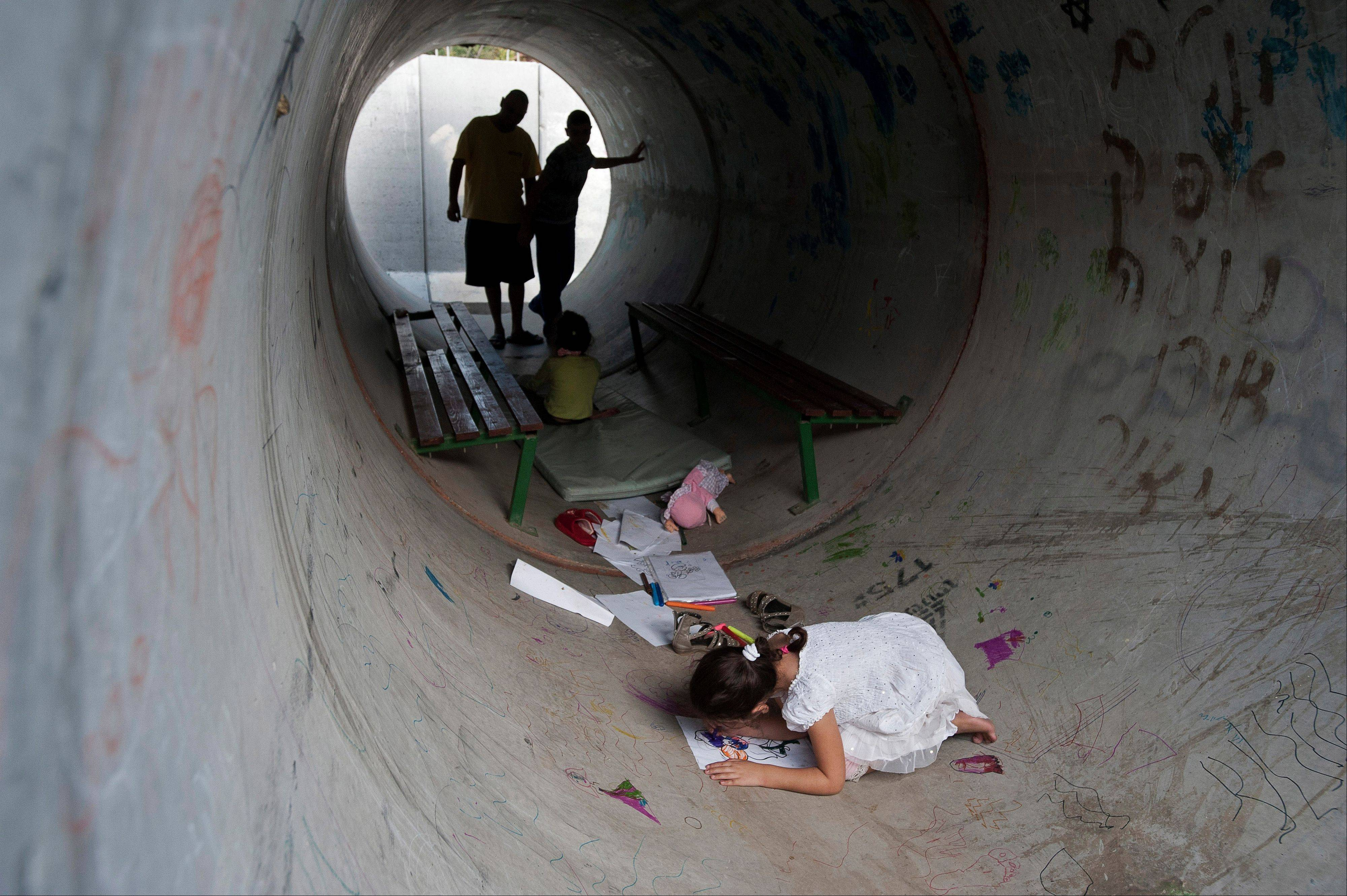 Israelis hide in a concrete tube during a rocket attack from Gaza, in Nitzan, southern Israel, Monday.