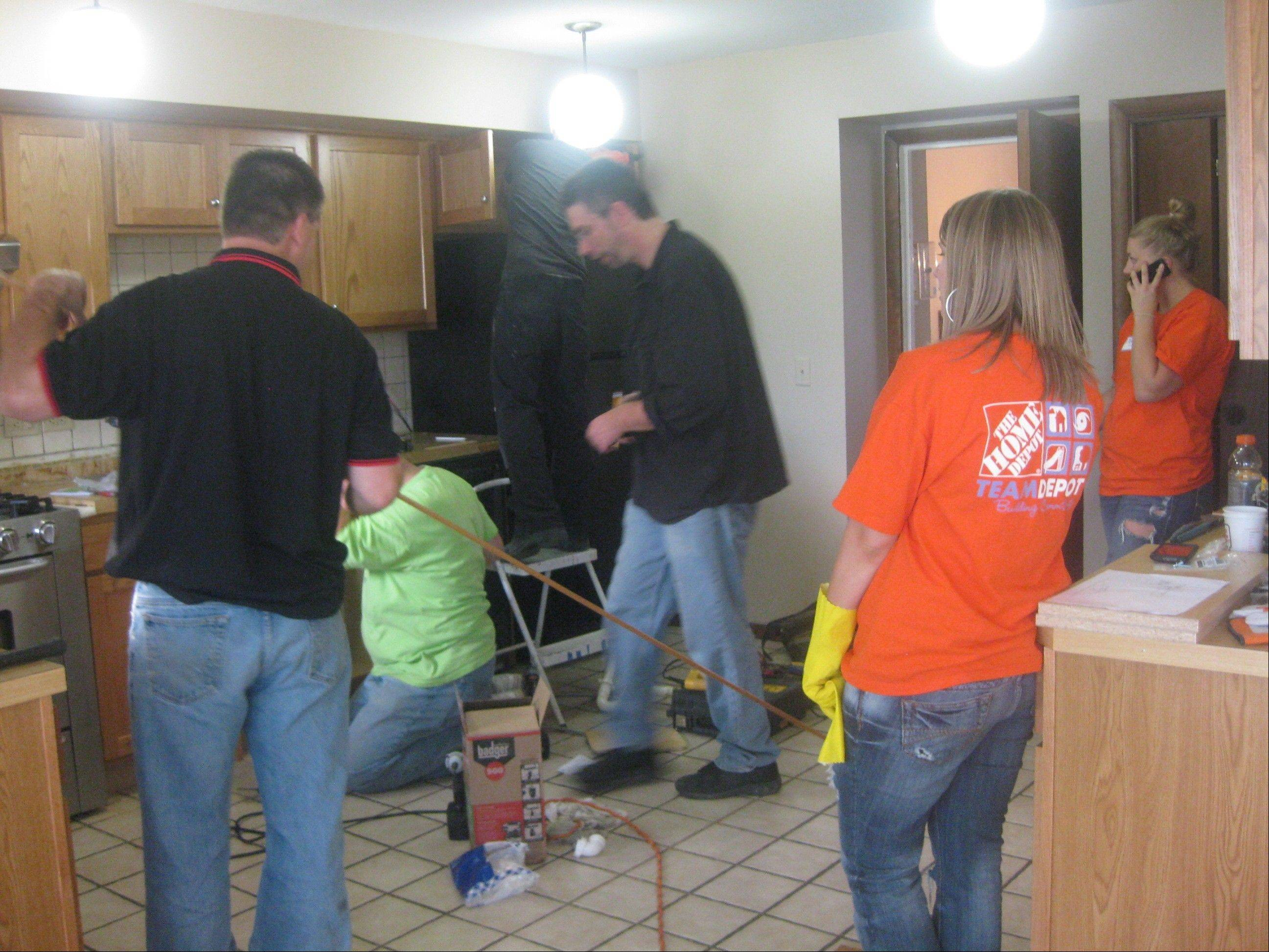 Volunteers from Home Depot work on remodeling a kitchen in a group home in Hoffman Estates for disabled adults that is operated by Clearbrook.