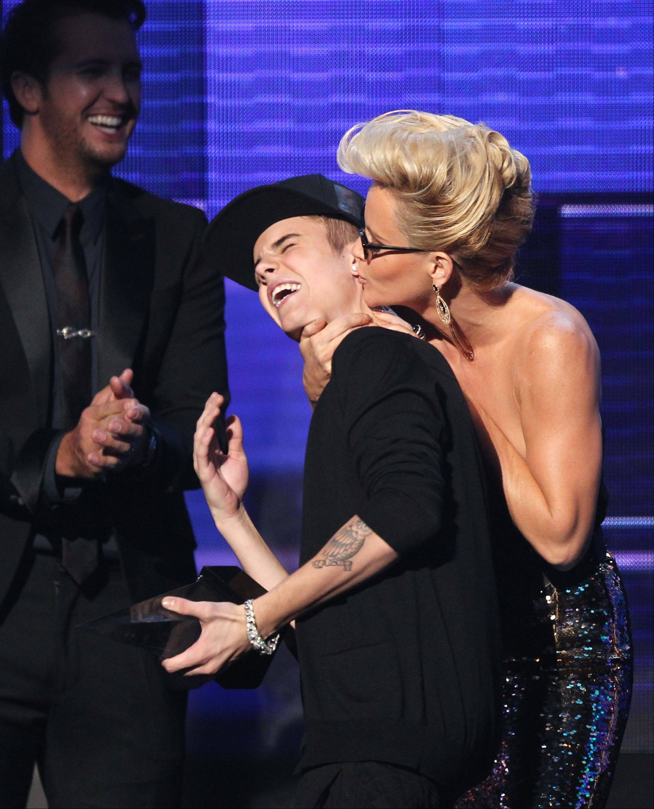Justin Bieber is smothered in kisses by presenter Jenny McCarthy as he accepts the award for favorite album - pop/rock for �Believe� at the 40th Anniversary American Music Awards Sunday night in Los Angeles.