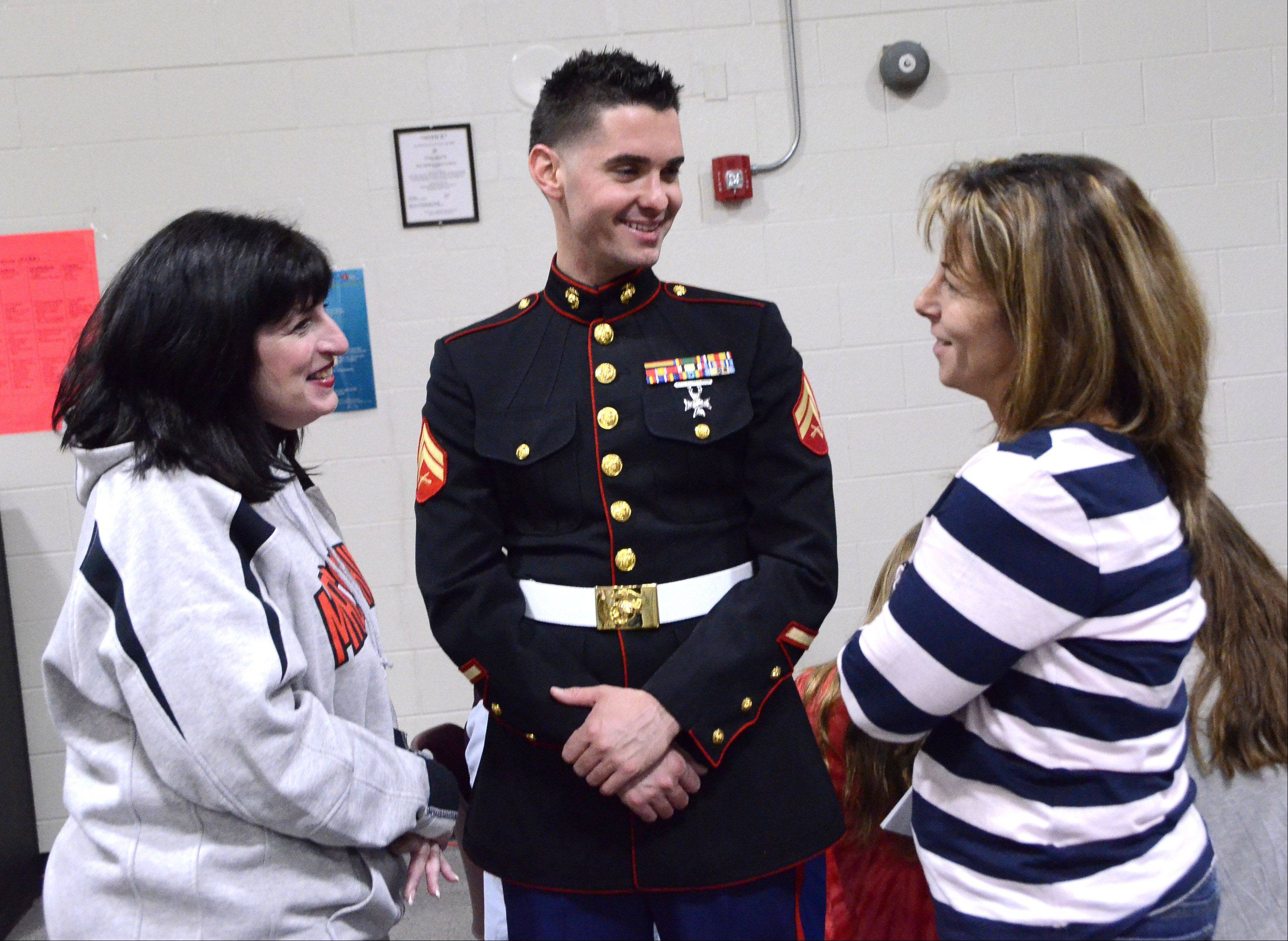 USMC Corporal Patrick Hood of Chicago, visits with his former teachers Jodi Hernandez, left, and Athena Lalaras at the Veterans Day breakfast and assembly Friday at MacArthur Middle School in Prospect Heights.