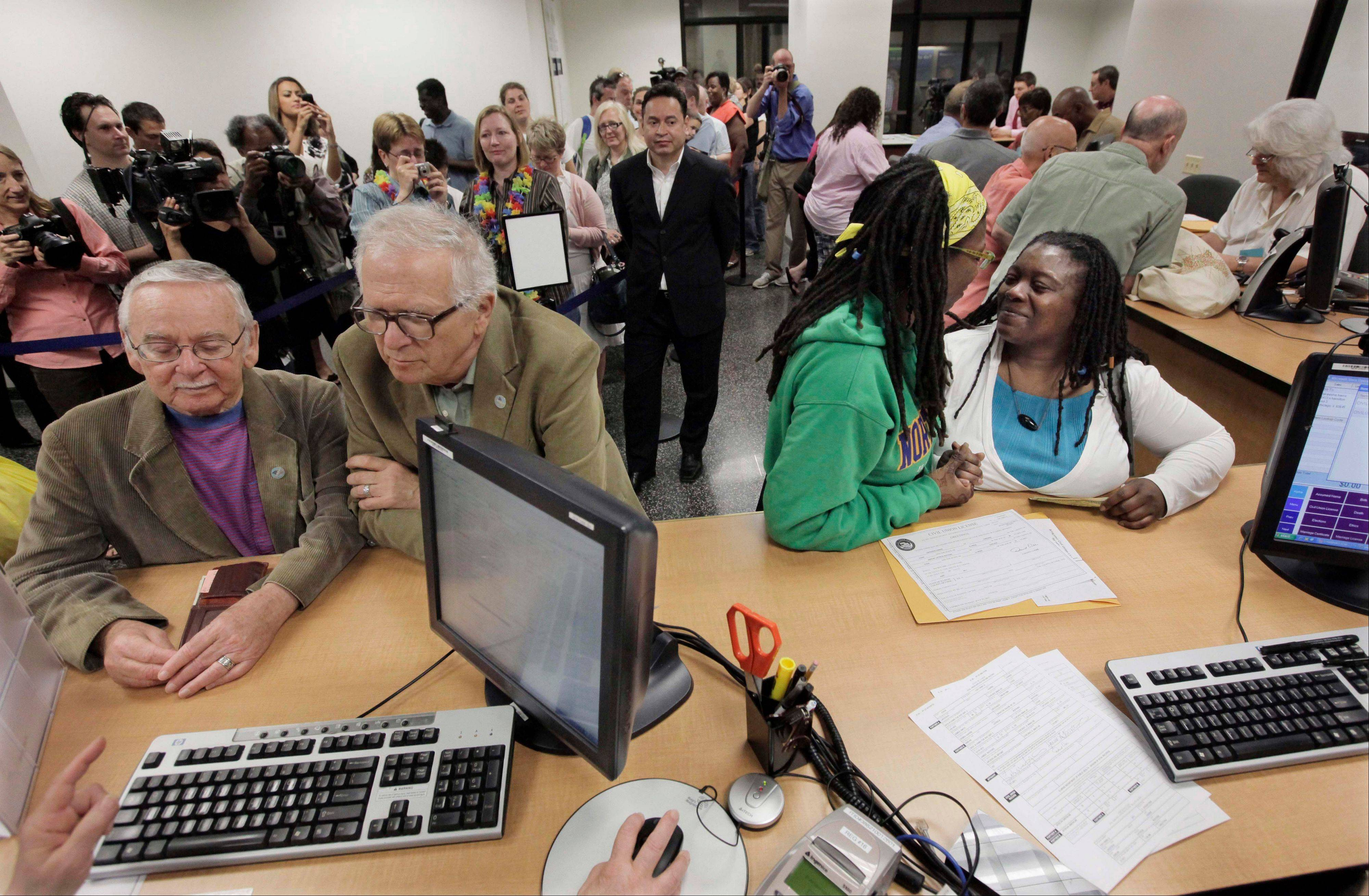 From left, Jim Darby, 79, and partner Patrick Bora, 73, and Janean Watkins, 37, and partner Lakeesha Harris, 36, wait in line at the Cook County Office of Vital Records to obtain civil union licenses on June 1, 2011.