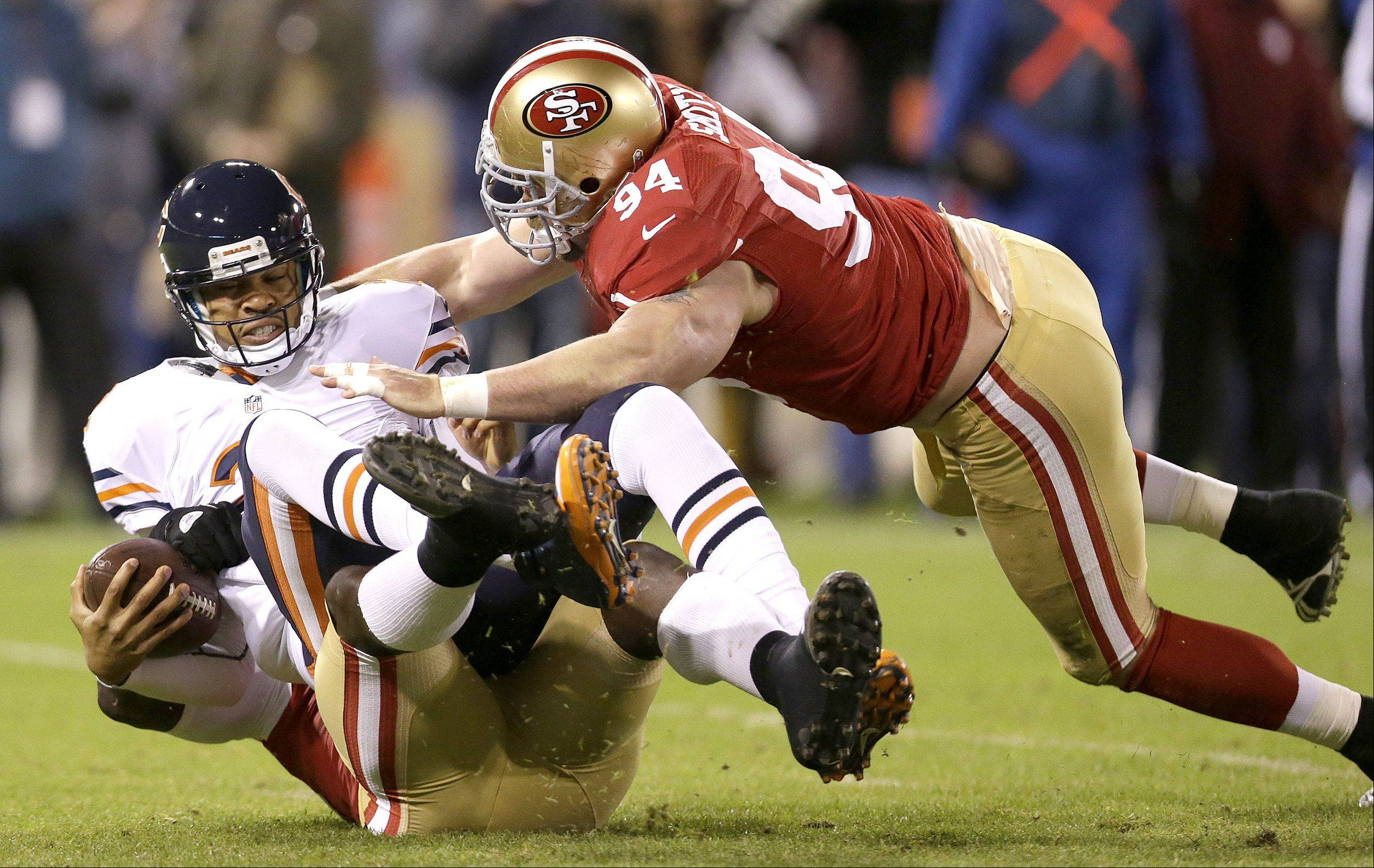 Chicago Bears quarterback Jason Campbell is sacked by San Francisco 49ers linebacker Aldon Smith, bottom, as defensive tackle Justin Smith converges during the first quarter.