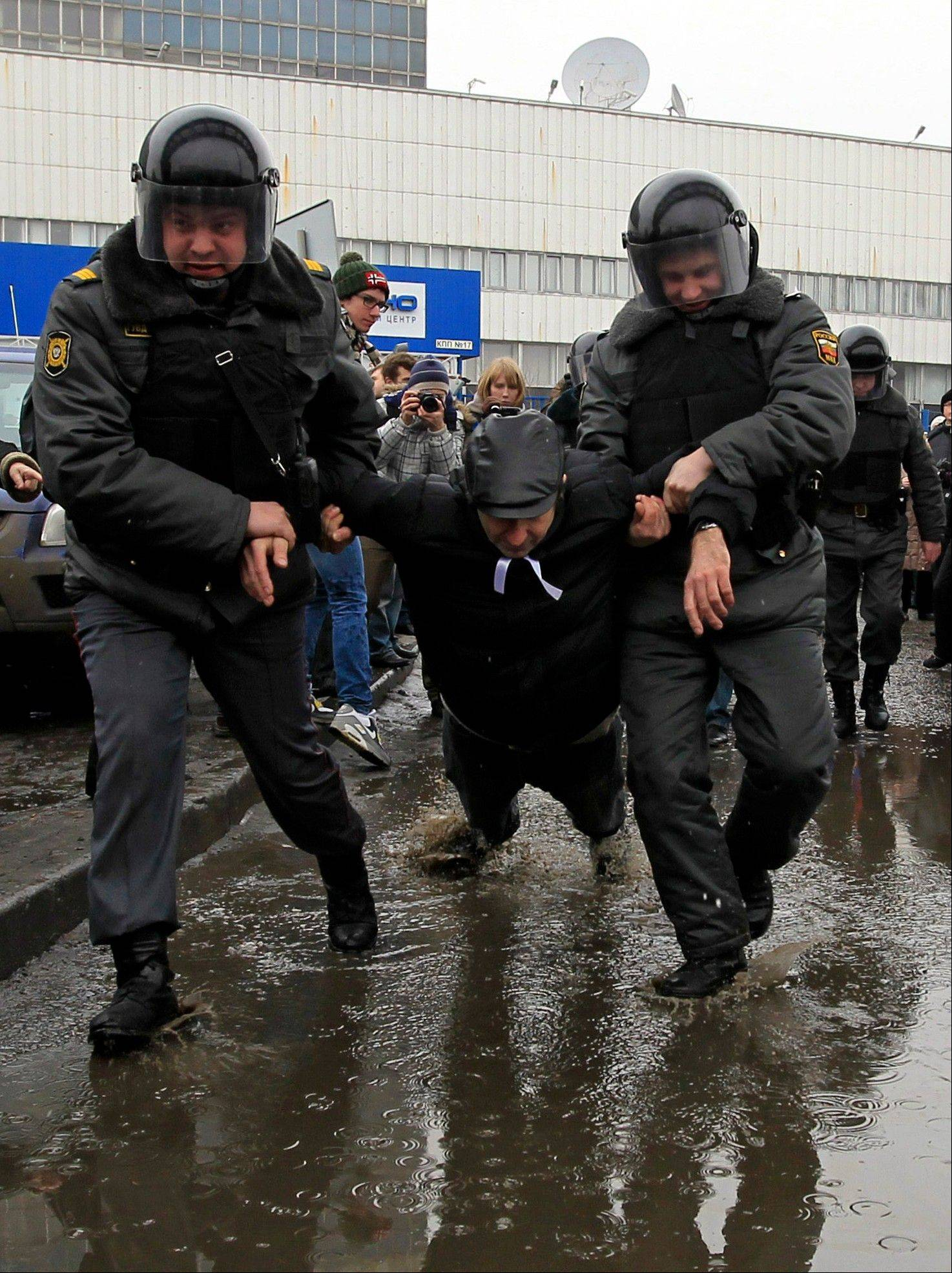 "Police officers detain a protester outside the Kremlin-loyal NTV television station in Moscow. Russian opposition and human rights groups on Monday, Nov. 19, 2012, urged Western consumer products giants to stop ""financing politically motivated persecution"" by advertising on a Kremlin-friendly TV network known for its biased coverage of government critics and demonstrations against President Vladimir Putin."
