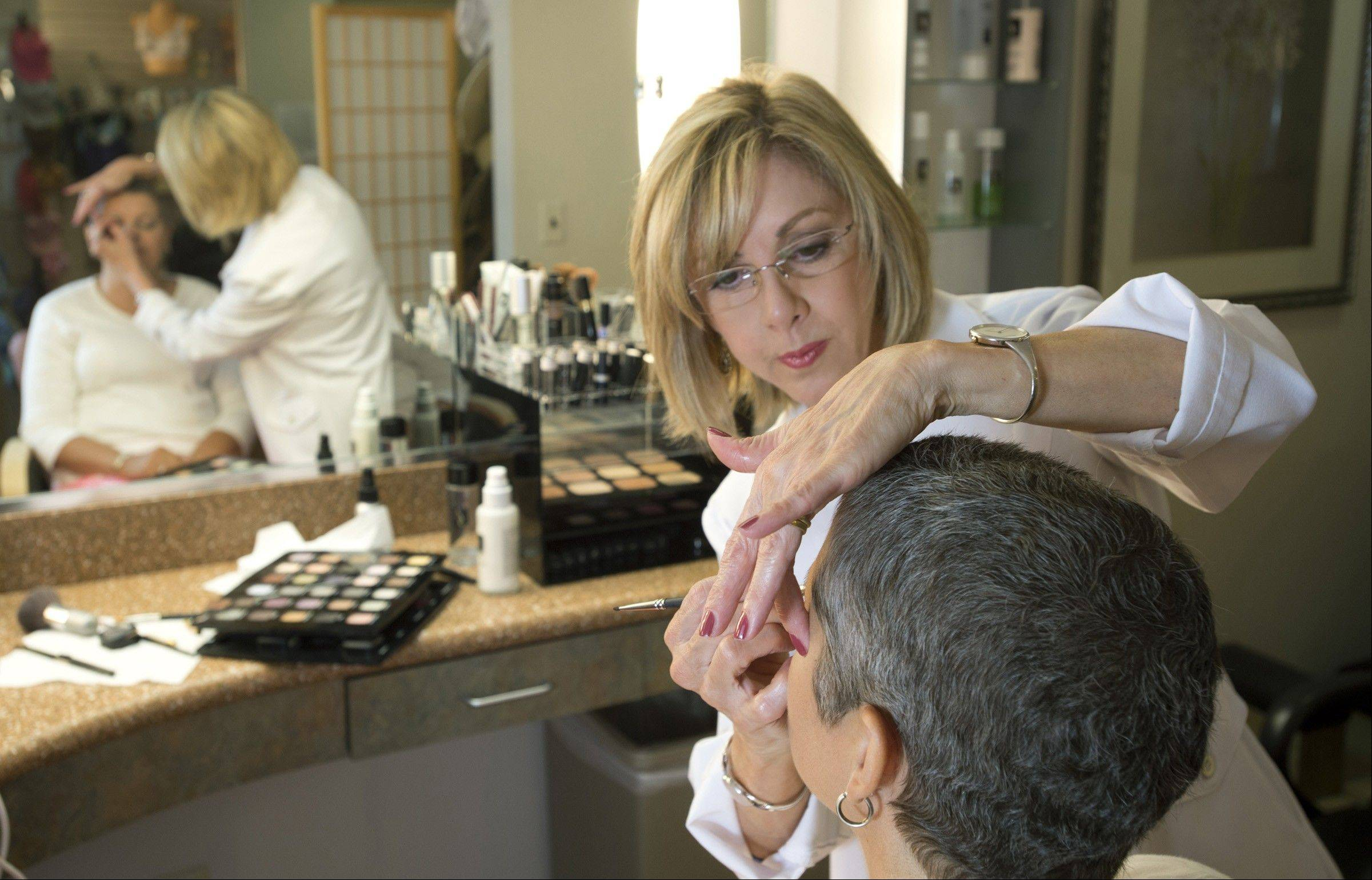 Marianne Kelly applies makeup to patient Debra Fruehling of Indian Head, Md., at the Image Recovery Center, a beauty salon at Johns Hopkins Hospital in Baltimore, Md.