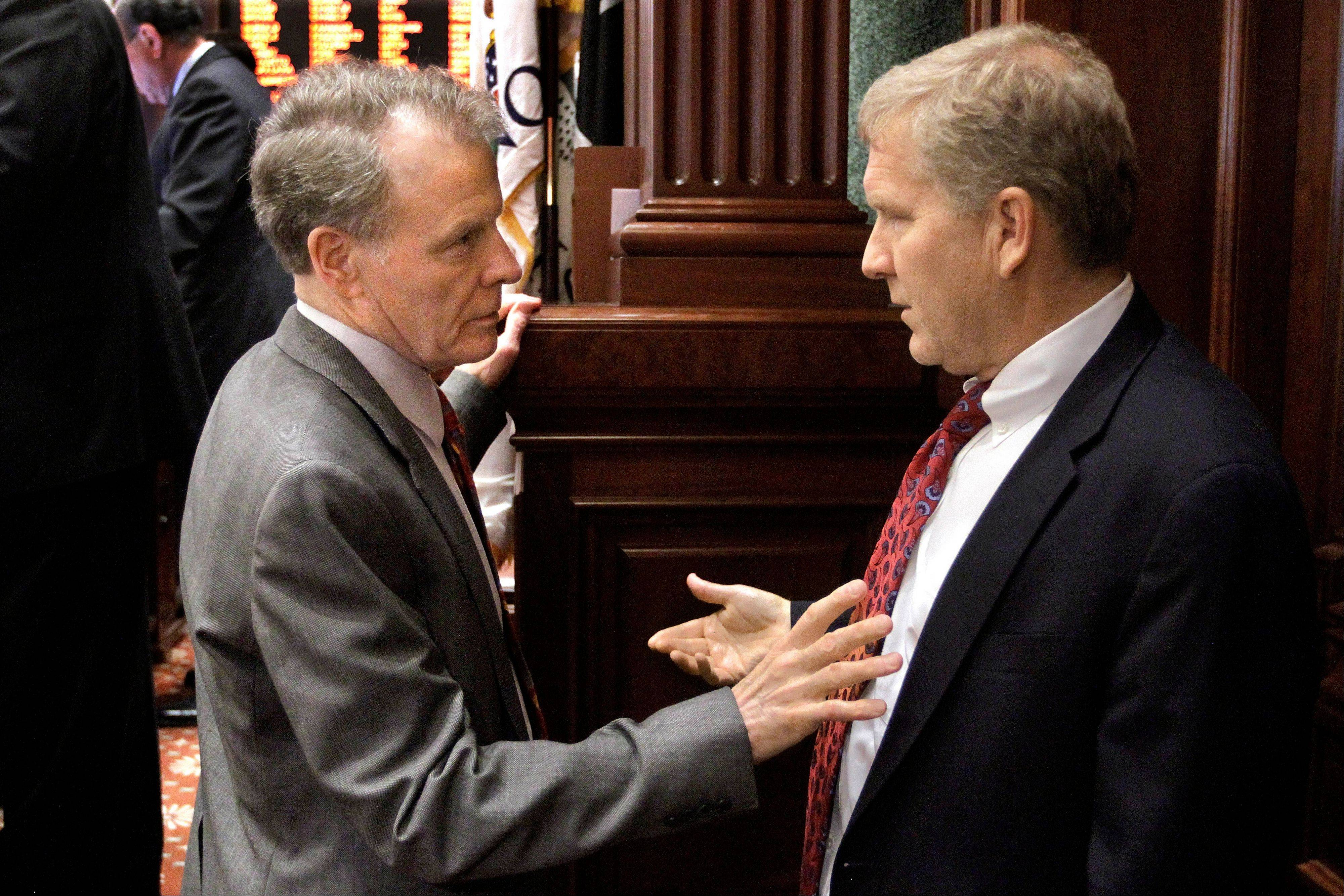 Illinois Speaker of the House Michael Madigan, left, speaks with Illinois House Minority Leader Tom Cross on the House floor during session at the Illinois State Capitol last May.