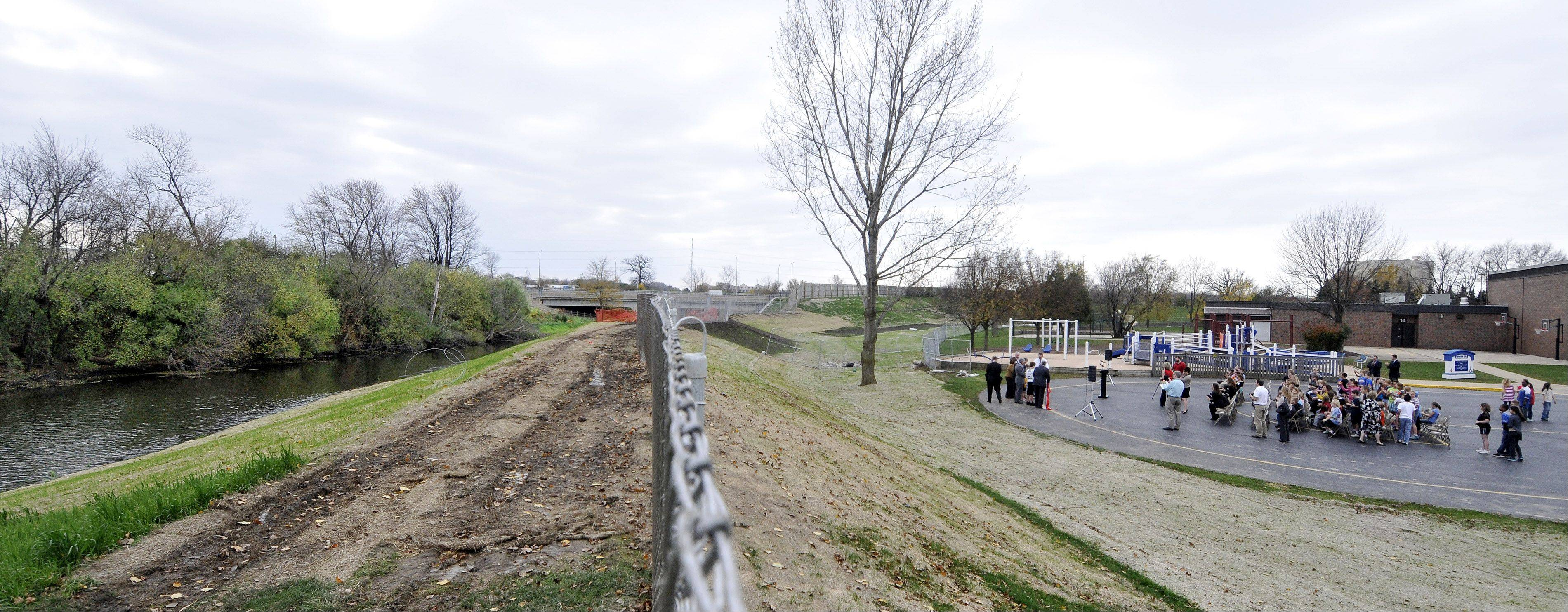 Bower Elementary School officials and students cut a ribbon in an area that flooded four years ago. To prevent future flooding, the school district and county worked together to build a new berm between the DuPage River and the Warrenville school.
