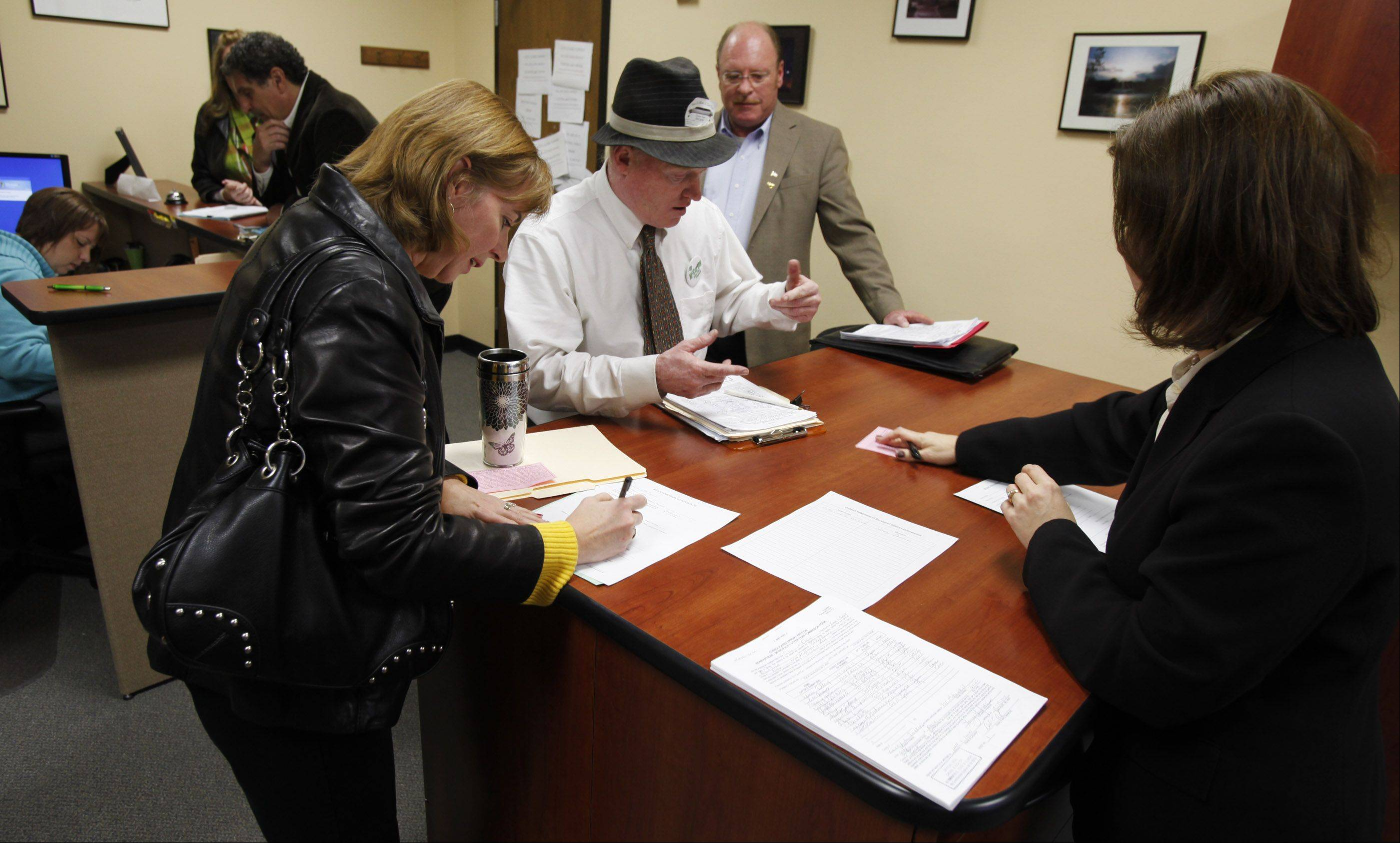 Elgin City Clerk Kimberly Dewis, right, helps candidates file their paperwork early Monday morning at Elgin City Hall. From left are Judy Dunne (filing for her husband, Councilman Richard Dunne), Tom McCarthy and Terry Gavin.