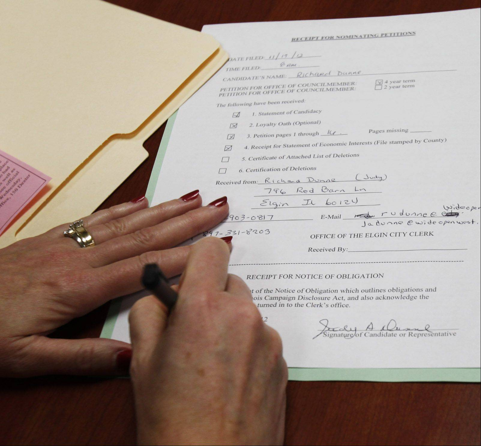 Judy Dunne signs the paperwork to make her husband's re-election bid official at the city clerk's office Monday morning.