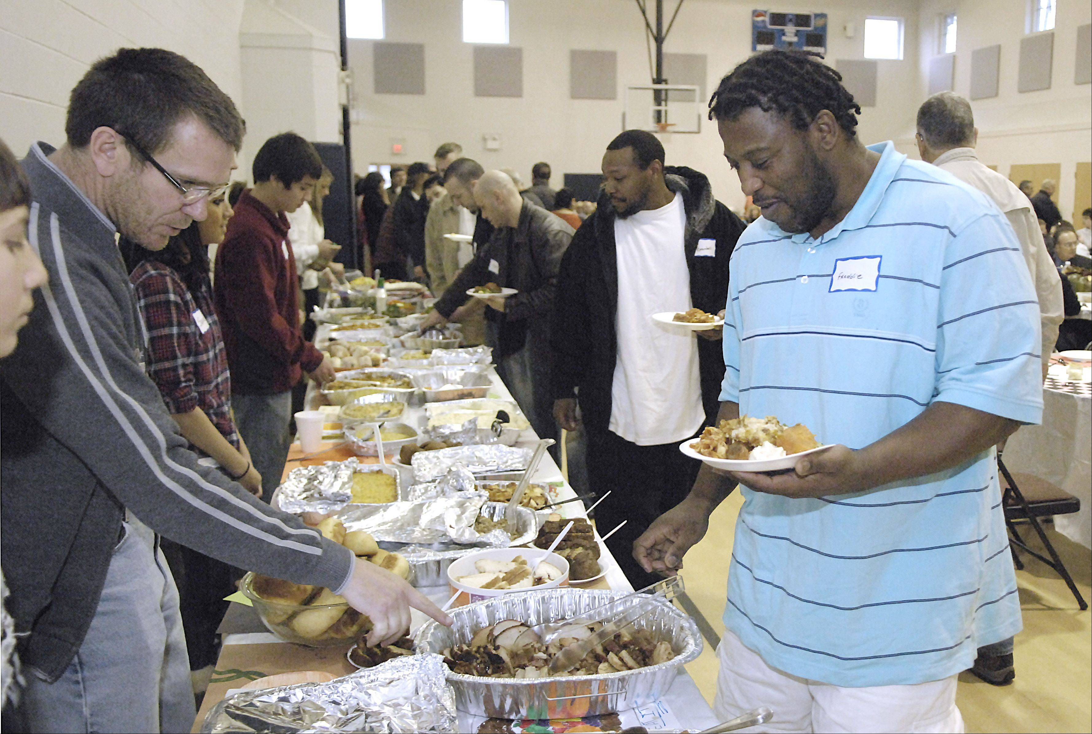 Volunteer John Myall of St. Charles directs Freddie Parson of Carpentersville toward some pork for his plate at the Lazarus House Community Feast in St. Charles on Thanksgiving Day last year.