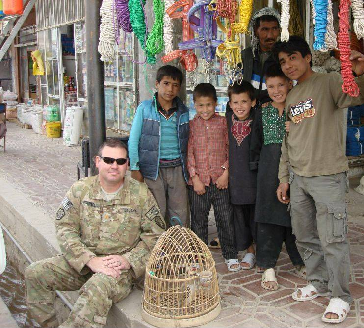 Mike O'Donnell is joined by a group of children at a bazaar in Bamyan City.  O'Donnell, an Army Reservist, is serving his third deployment overseas.