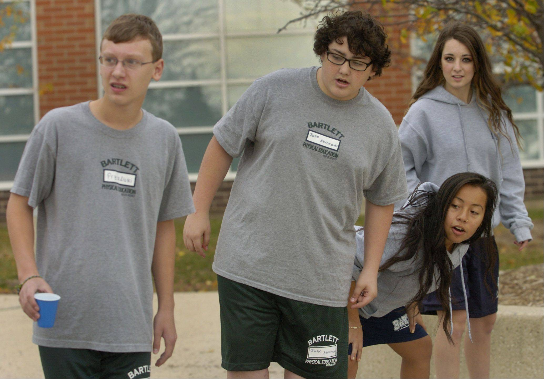 Leaders Selena Cuevas and Cecily Herby, right, guide freshmen Kyle Przislicki, left, and Jake Alvarado through a team-building exercise as part of Bartlett High School's senior leaders program.