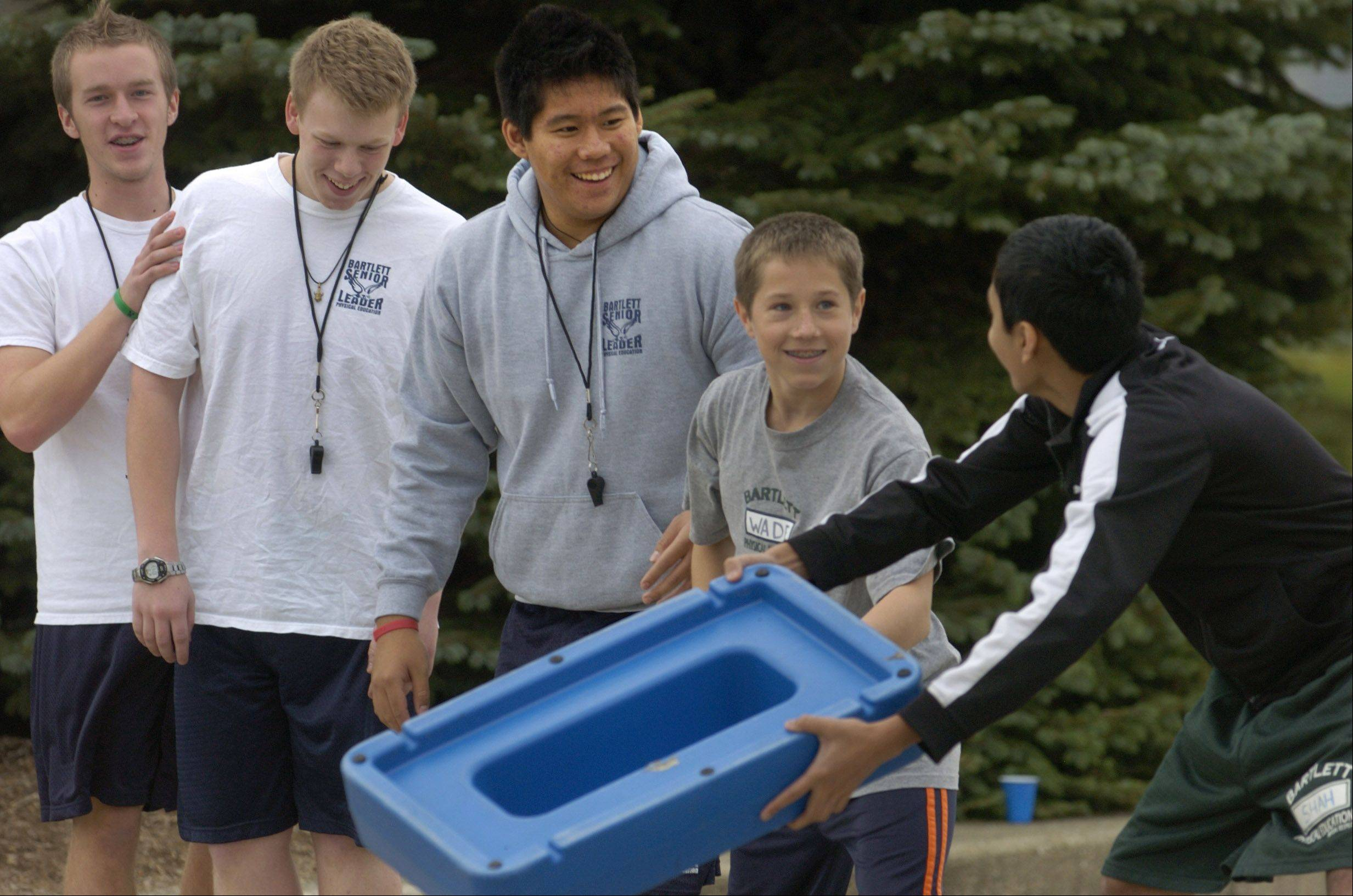 Seniors, from left, Nick LoBosco, Alex Schwartz and Pierce Tinio, help freshmen Jacob Wade and Miten Shah with a team-building exercise called Raging River, as part of Bartlett High School senior leaders program.