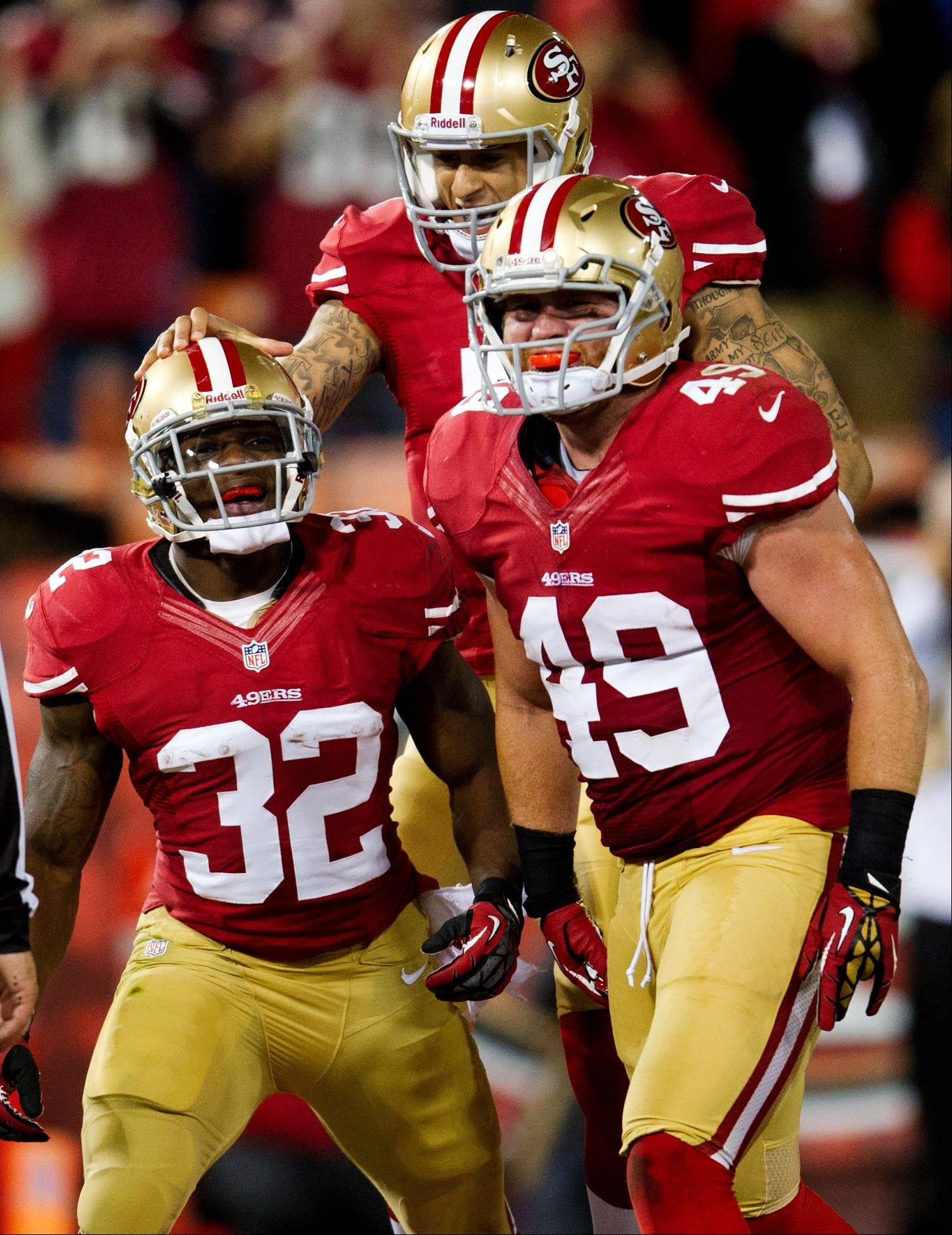 San Francisco 49ers running back Kendall Hunter celebrates with fullback Bruce Miller and quarterback Colin Kaepernick after his touchdown against the Chicago Bears during the second quarter.