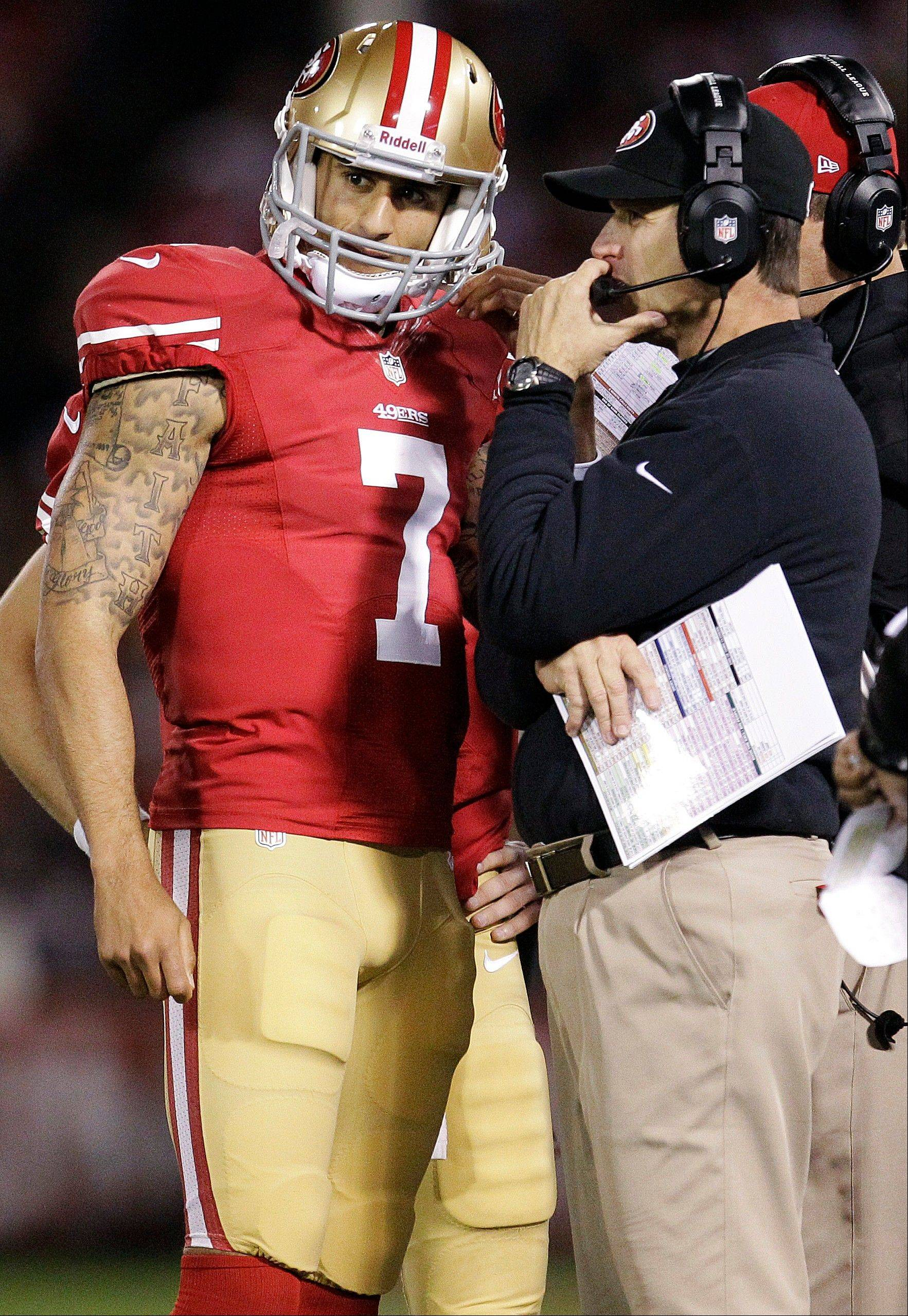 San Francisco 49ers quarterback Colin Kaepernick talks with head coach Jim Harbaugh during the first half.