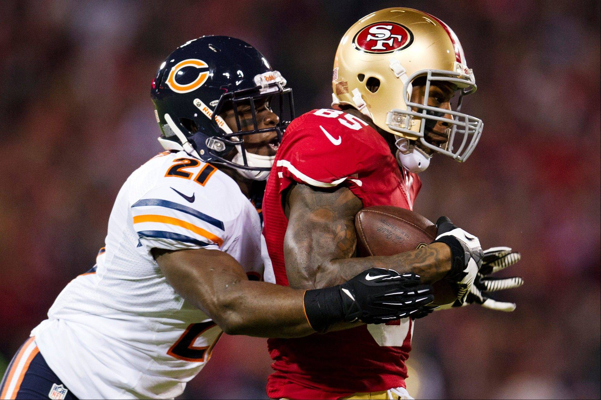 San Francisco 49ers tight end Vernon Davis completes a 22-yard pass reception as he is tackled by Chicago Bears strong safety Major Wright during the first quarter .