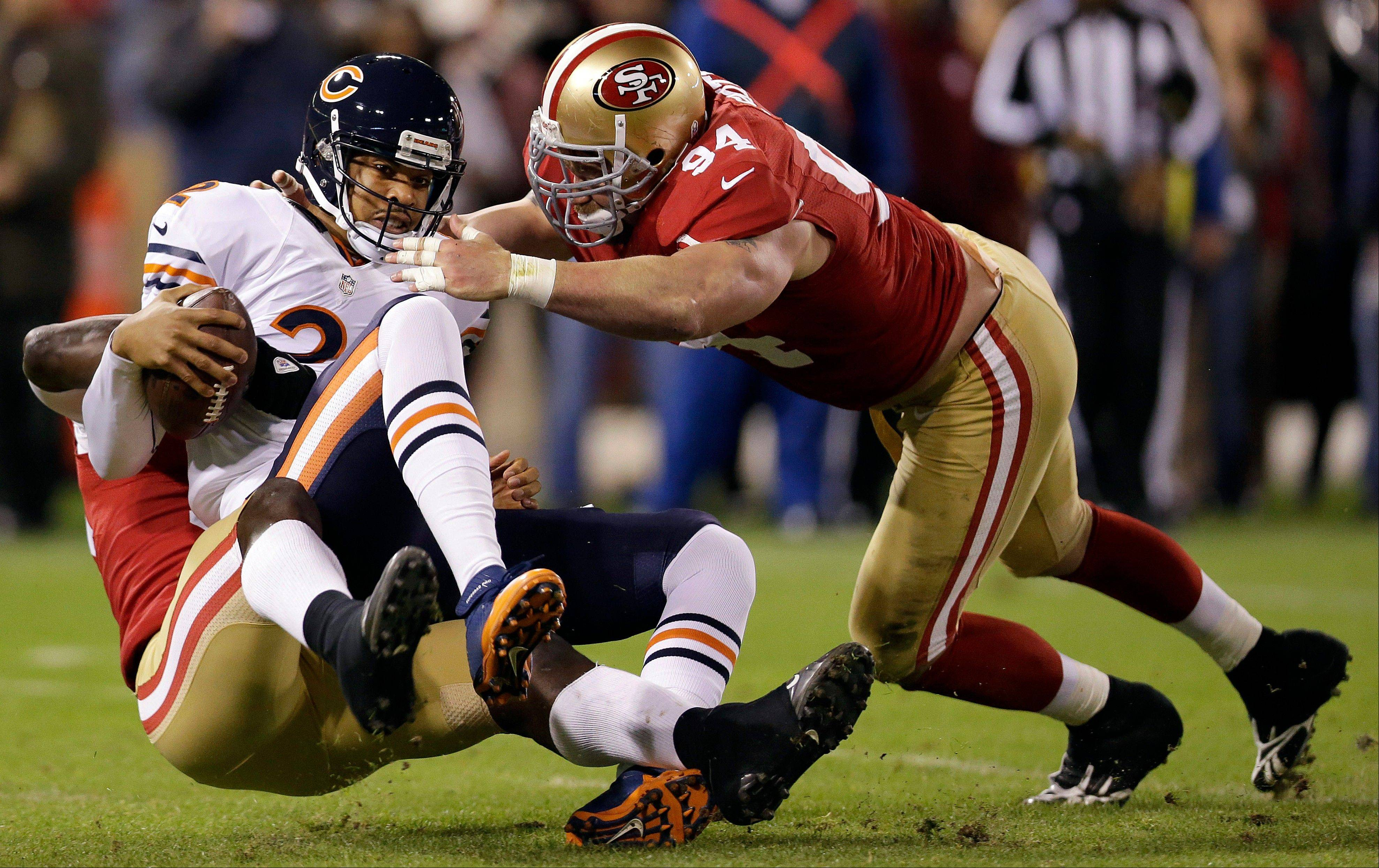 Chicago Bears quarterback Jason Campbell is sacked by San Francisco 49ers linebacker Aldon Smith, left, as defensive tackle Justin Smith converges during the first quarter.