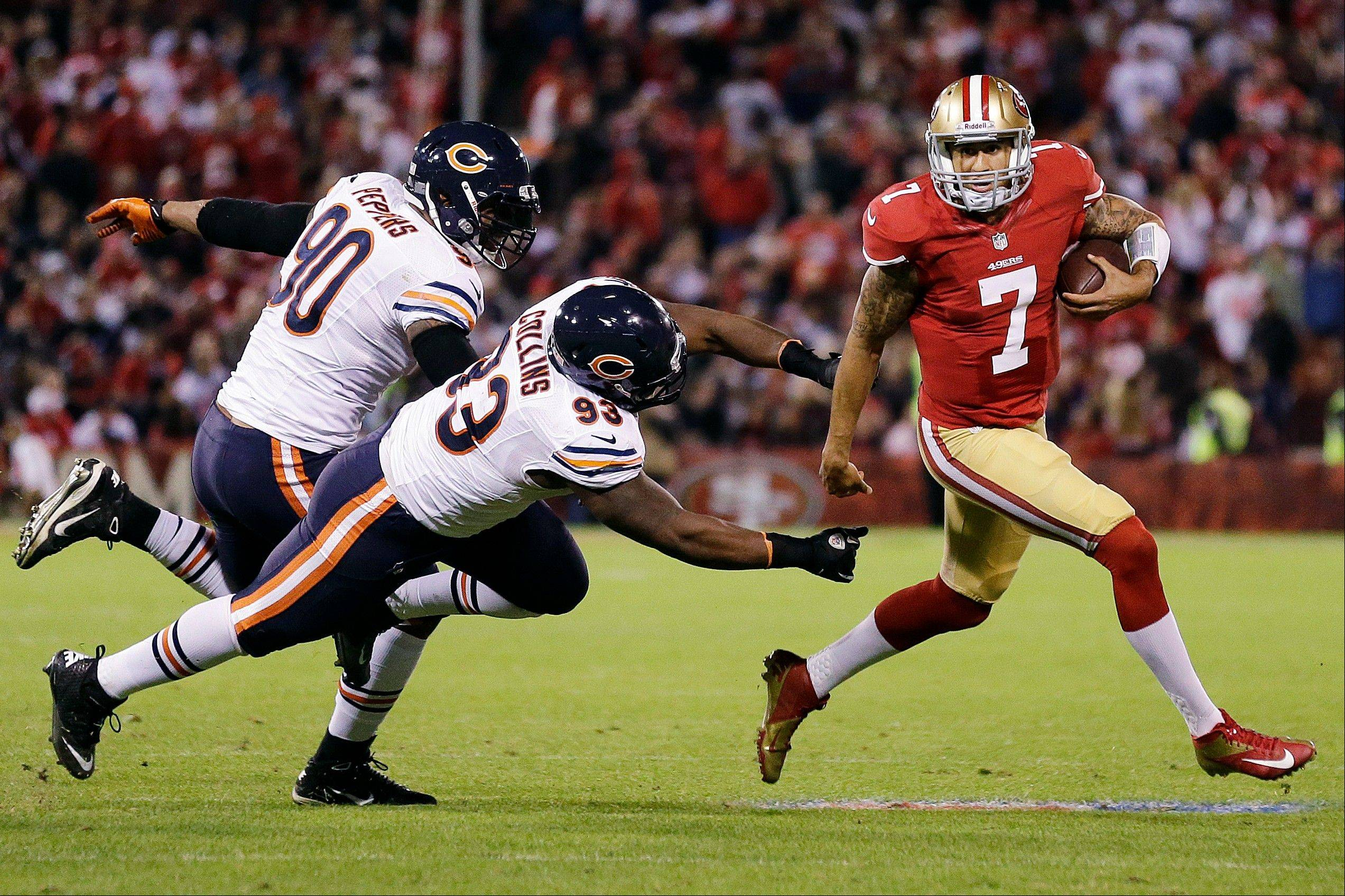 San Francisco 49ers quarterback Colin Kaepernick runs away from Chicago Bears defensive end Julius Peppers and defensive tackle Nate Collins during the third quarter.